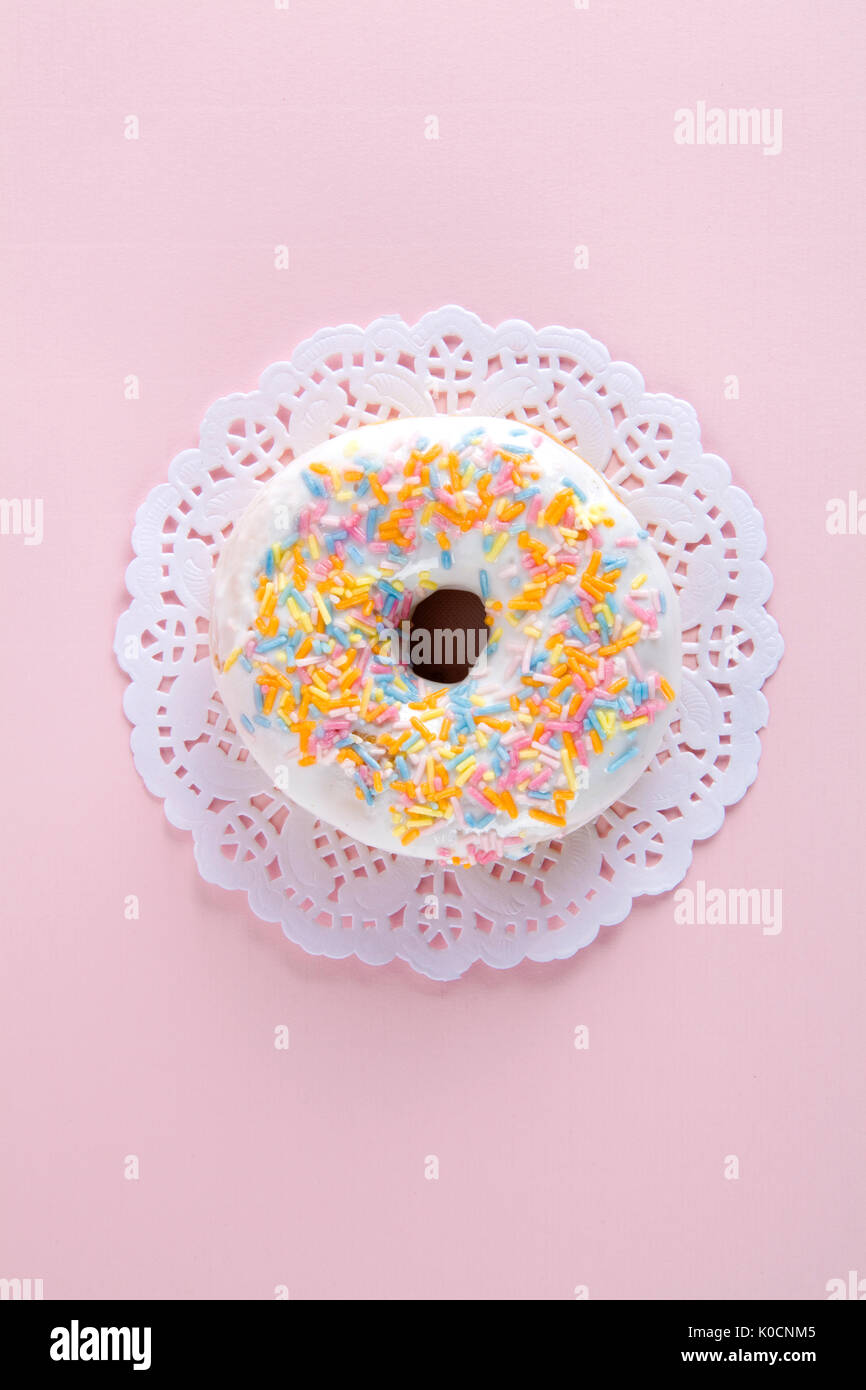 a multicolor donuts presented on a doily paper and a pop colorful background. - Stock Image