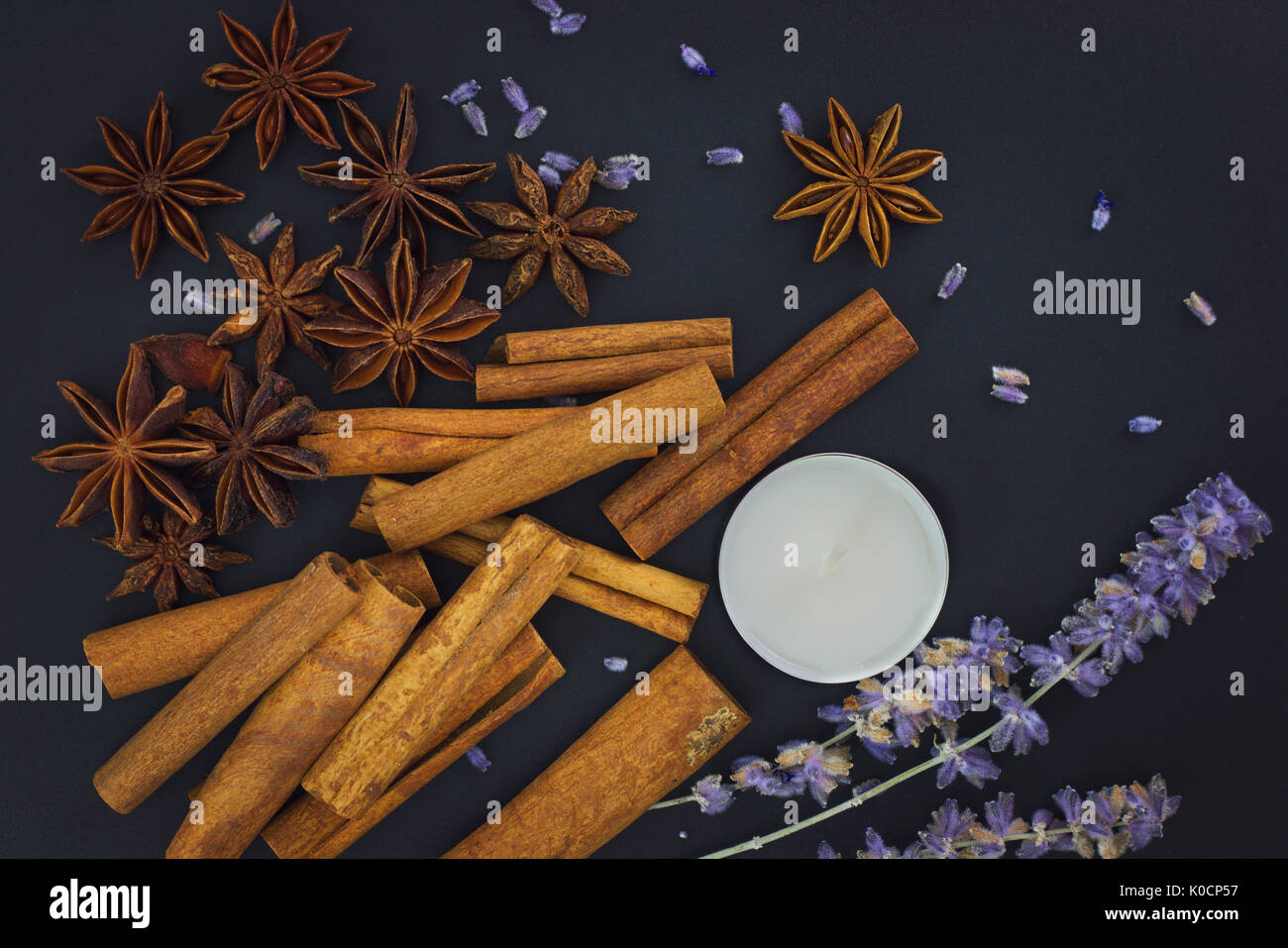 Sense of Spices cinnamon and star anise whit candle on black background with copy space - Stock Image