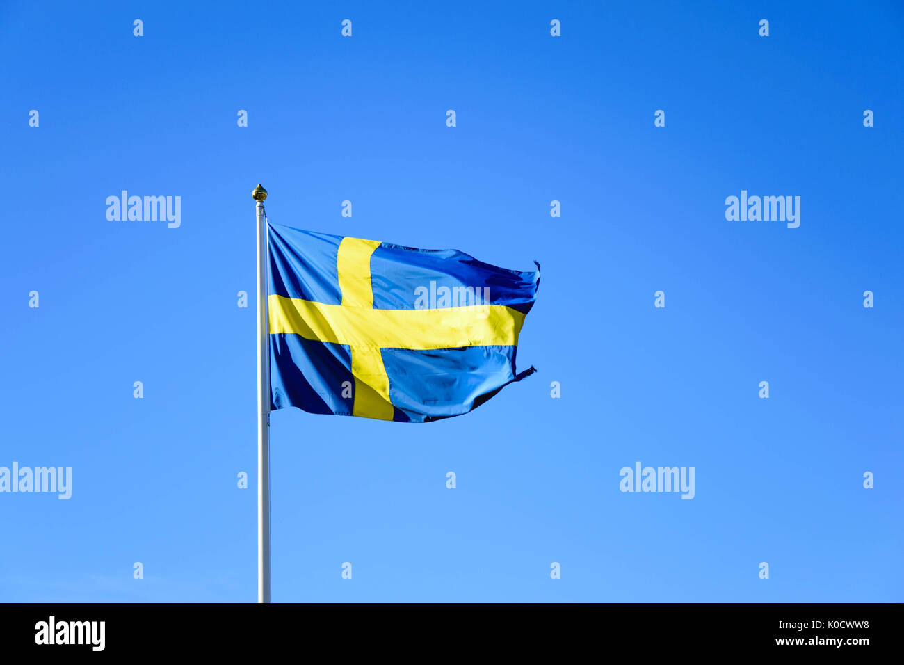Swedish flag waving in a clear blue sky. Taken with Nikon D5300 - Stock Image