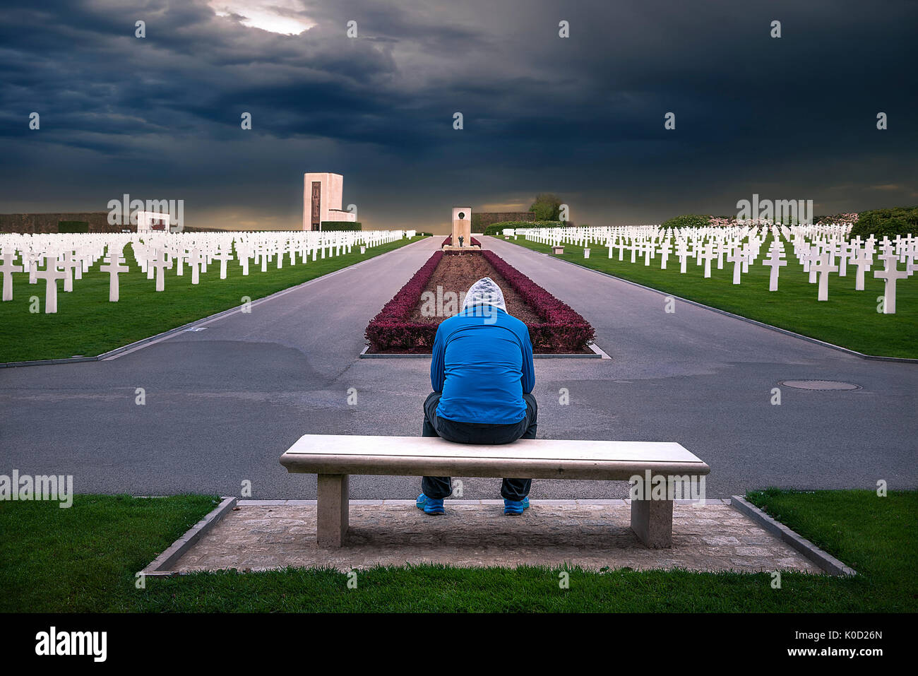 Man sitting on a bench and thinking about all the soldiers that are honored through this American memorial cemetery, located in Luxembourg. - Stock Image