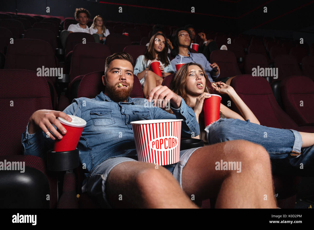 Impolite rude couple sitting in a cinema and chewing loudly while watching a movie - Stock Image
