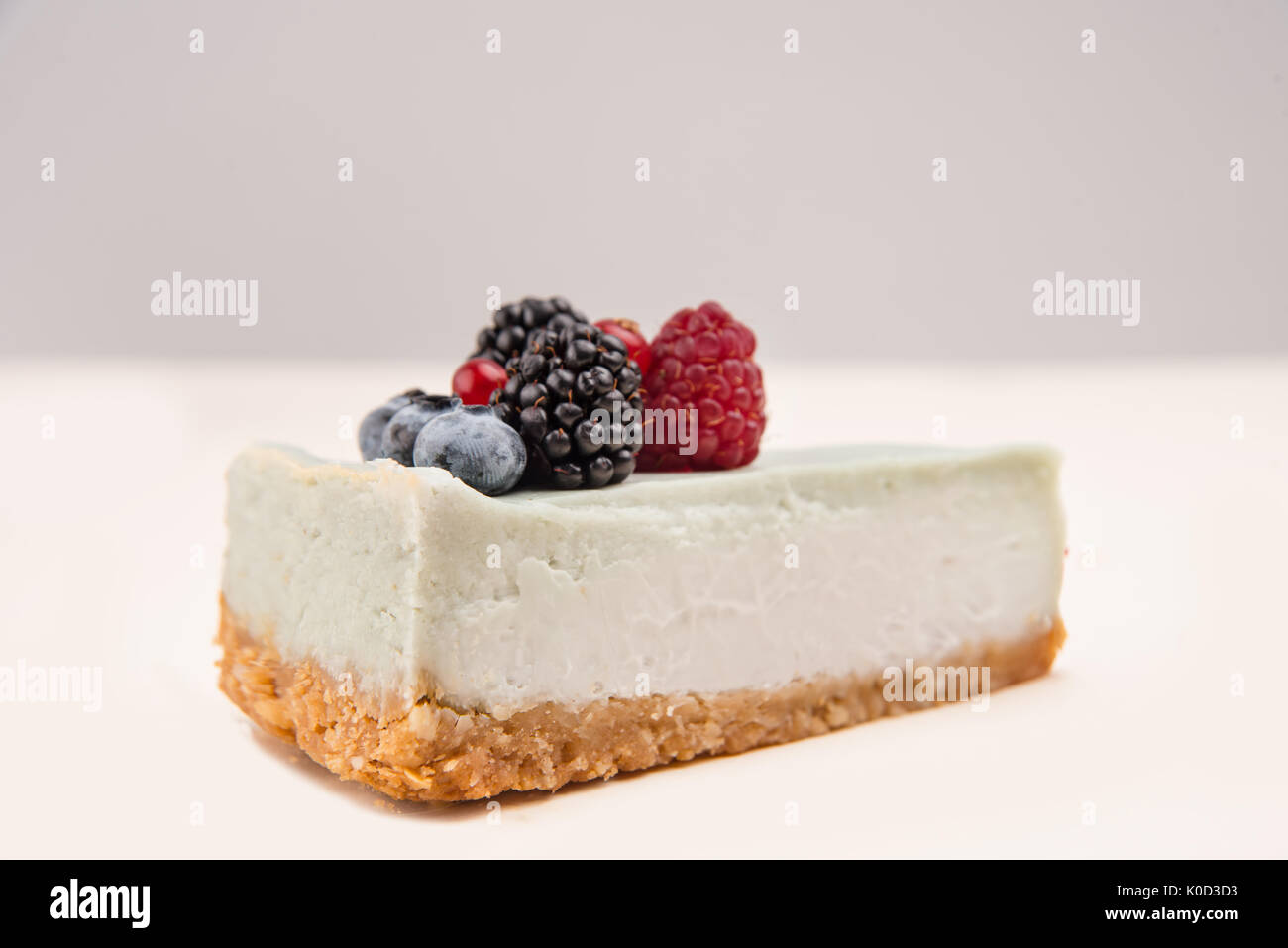 Side view of blue cheesecake with different berries on it isolated over white - Stock Image