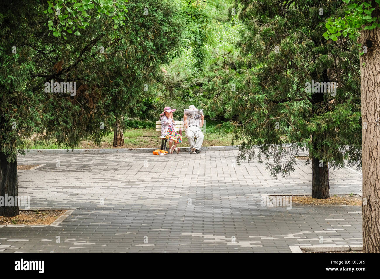 A retired Chinese couple reading newspapers at a quiet corner of the park - Stock Image