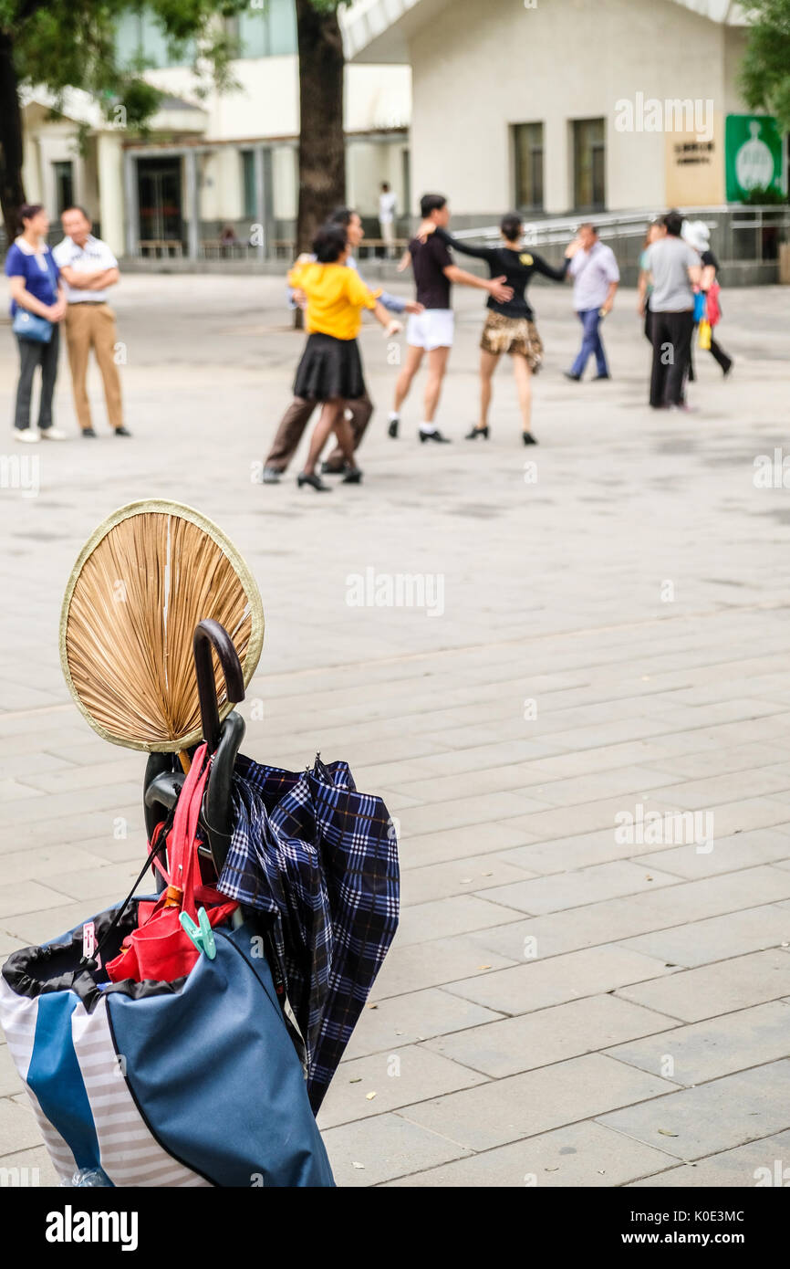 An old fashioned Chinese style straw fan in a pack, with men and women in modern dressings practicing Latin dances in the background in a park - Stock Image