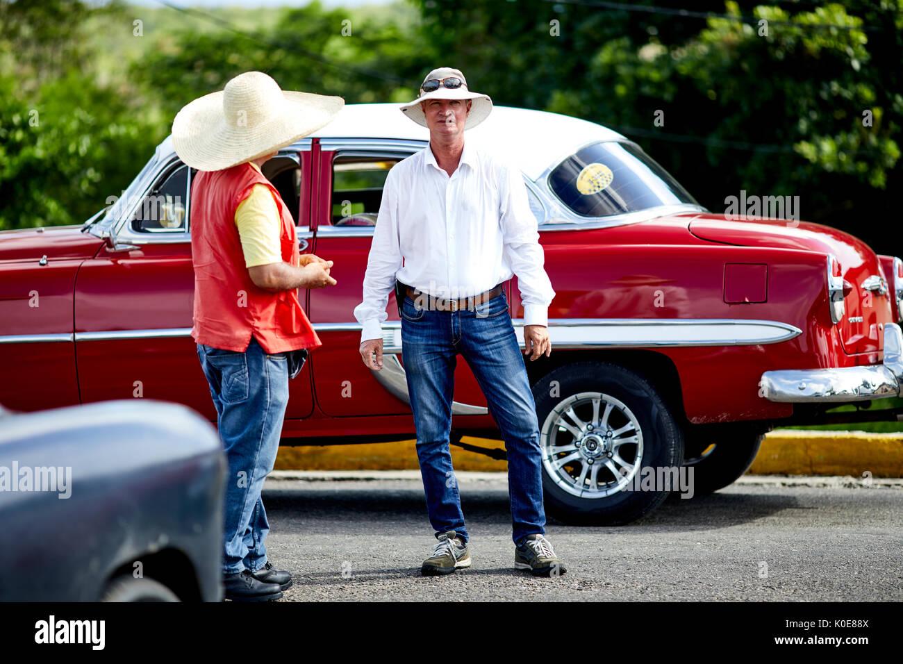 Cuban parking attendant with classic American car at  Bacunayagua Bridge, Cuba near Matanzas, Cuba, Caribbean island nation under communist rule - Stock Image