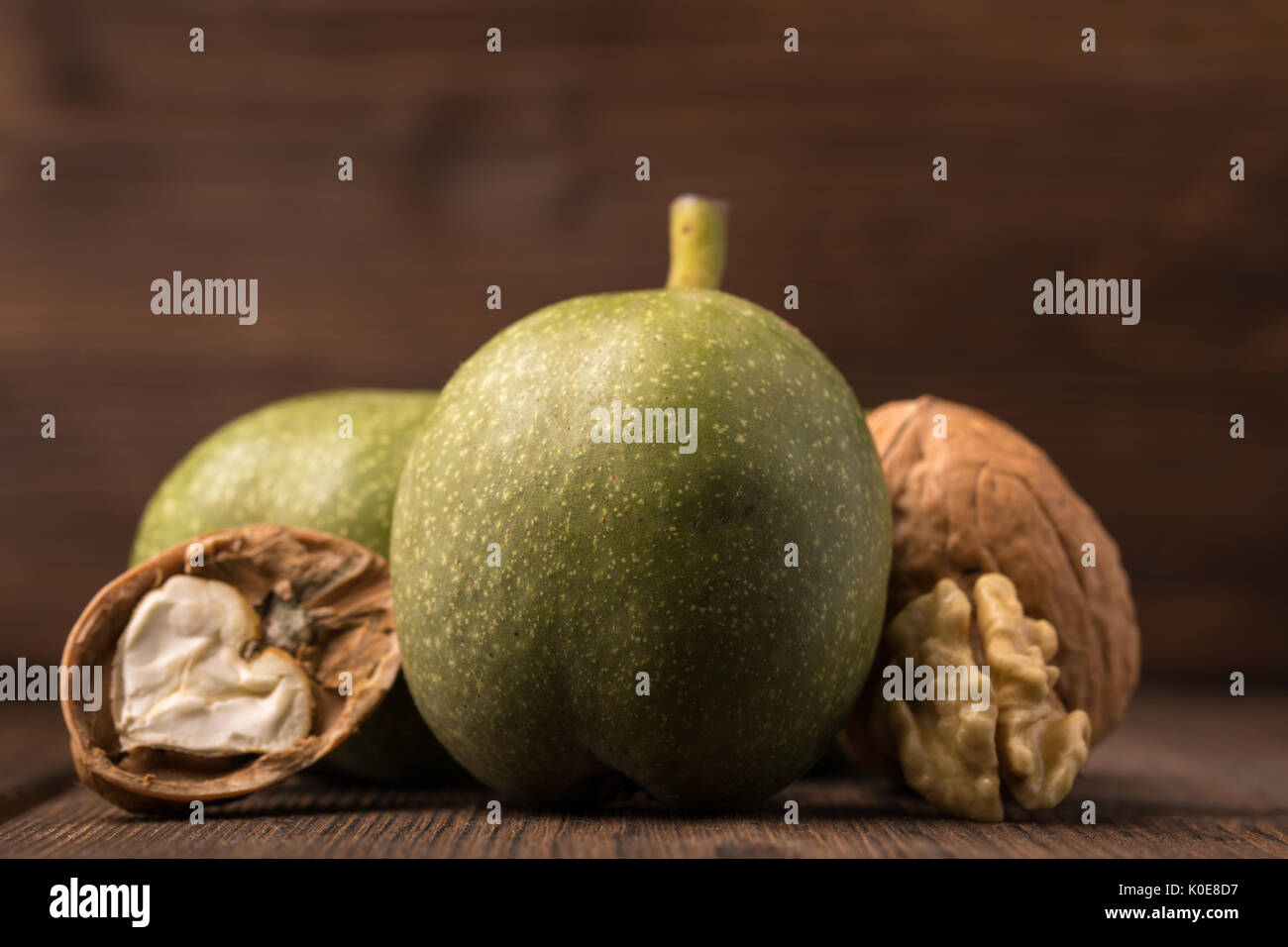 Fresh harvest of walnuts on a wooden background. Green and brown nuts. Shell and peel of walnuts. Walnuts on a wooden surface - Stock Image