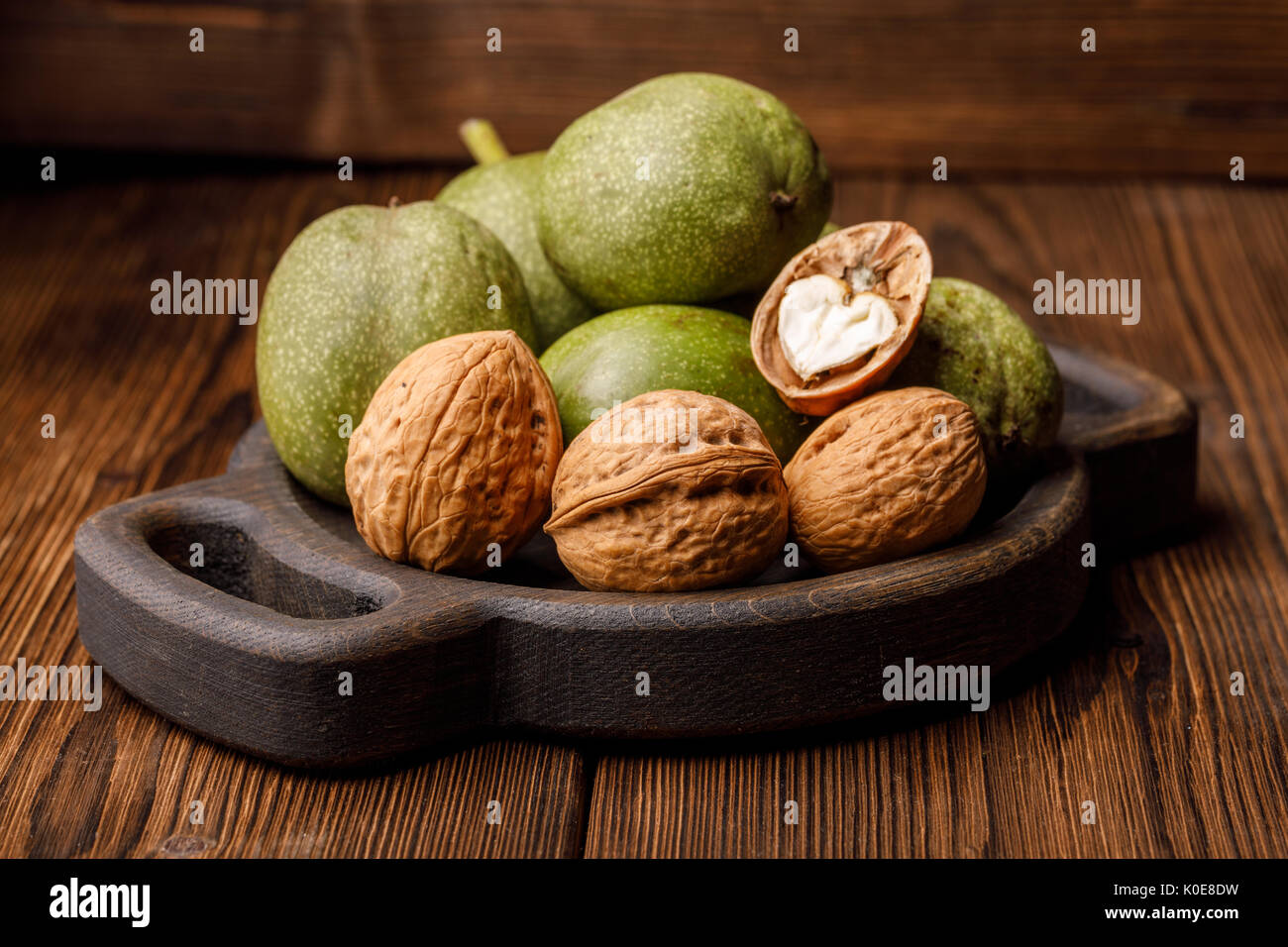 Fresh harvest of walnuts on a wooden background. Green and brown nuts on a beautiful wooden plate. Shell and peel of walnuts. Macro. - Stock Image
