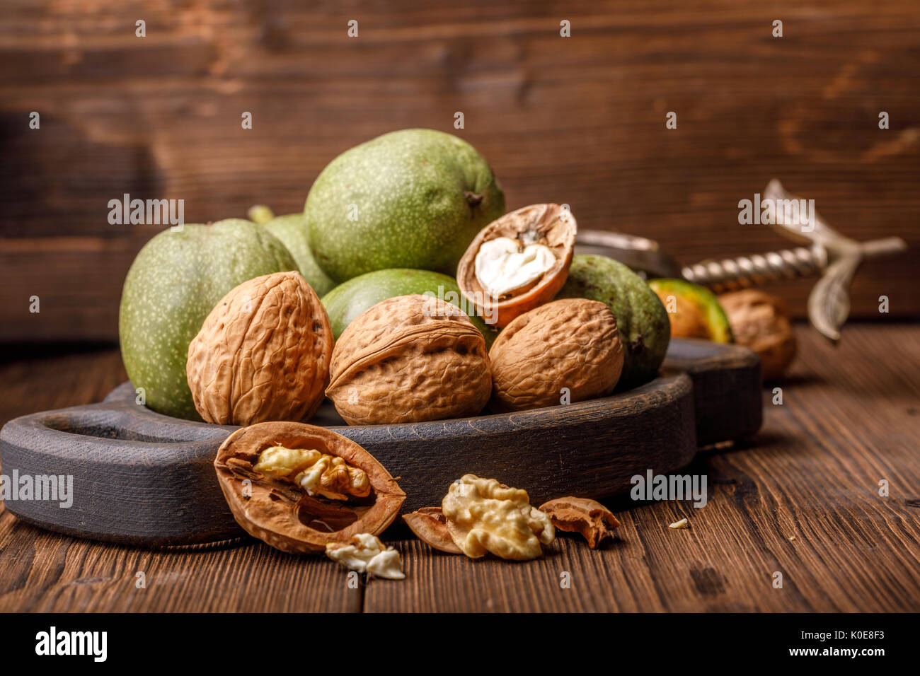 A handful of green young walnuts on a wooden background together with an old nutcracker. Nuts with shell and walnuts in green peel. - Stock Image