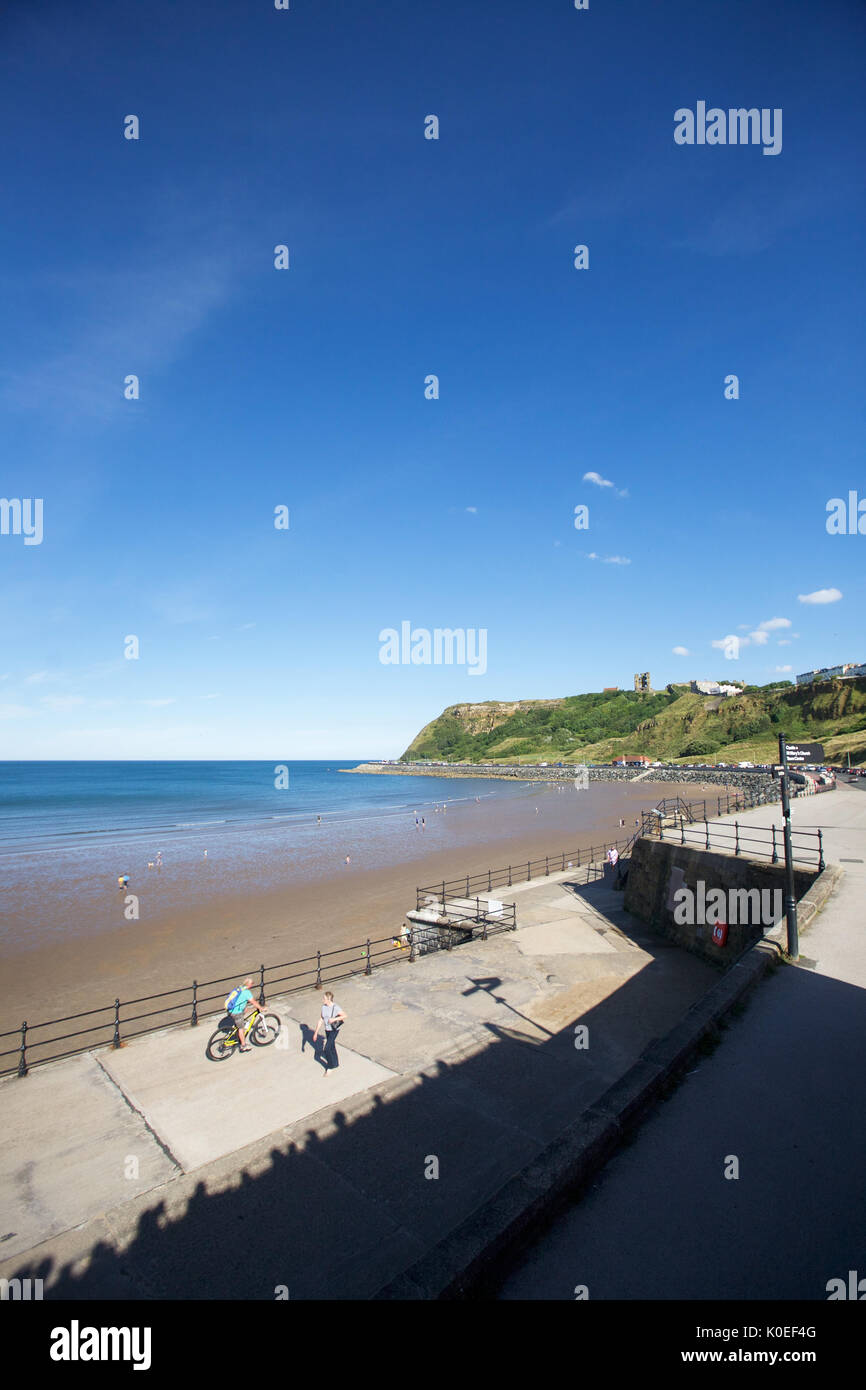 View of Scarborough Castle from North Bay Scarborough with cyclists and walkers on the promenade - Stock Image
