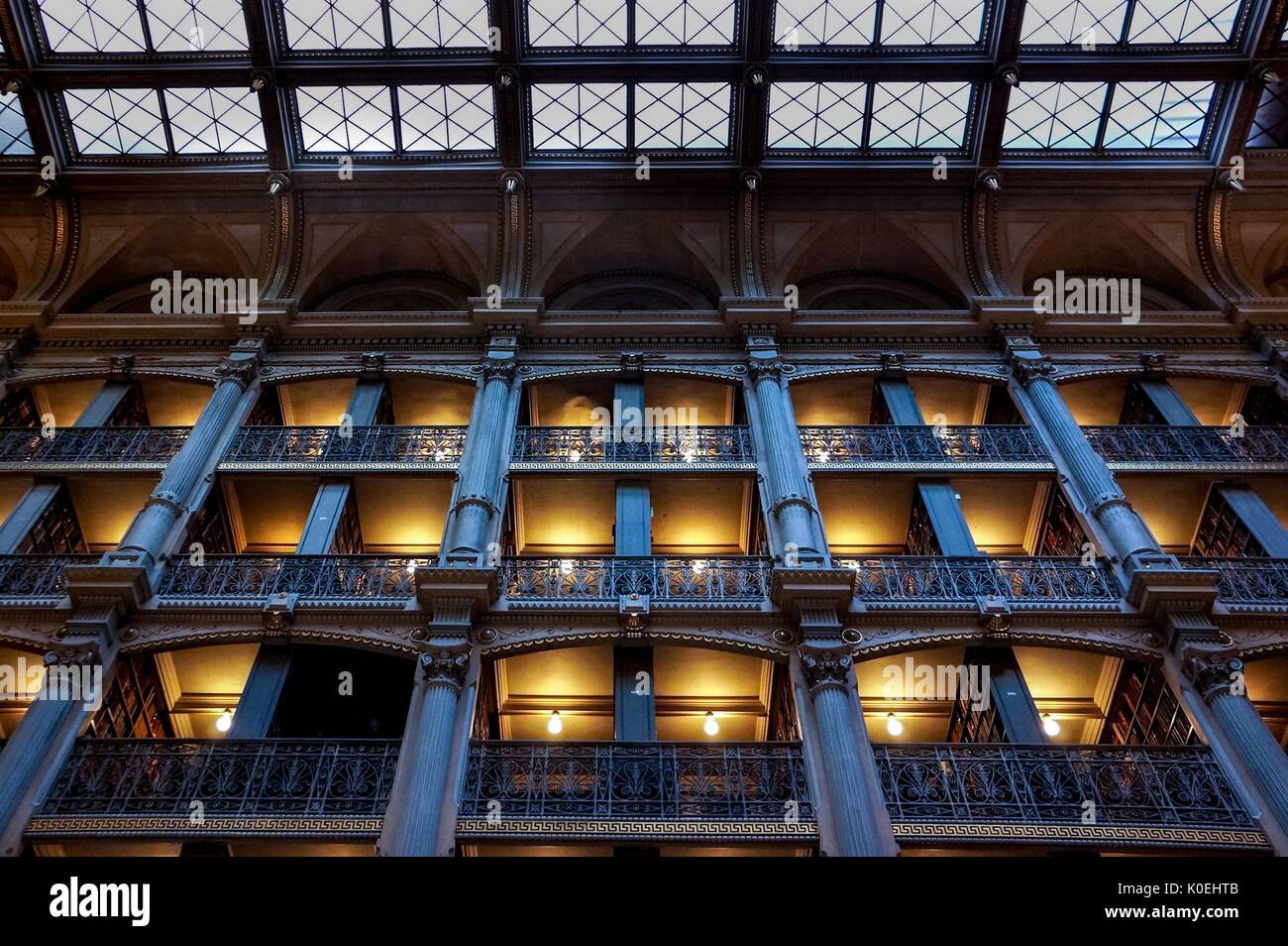 A low-angle shot of the levels of the George Peabody Library, a research library for Johns Hopkins University, with cast iron railings and exposed glowing light bulbs lighting the full bookshelves during the Baltimore Book Festival, Baltimore, Maryland, September 28, 2013. Courtesy Eric Chen. - Stock Image