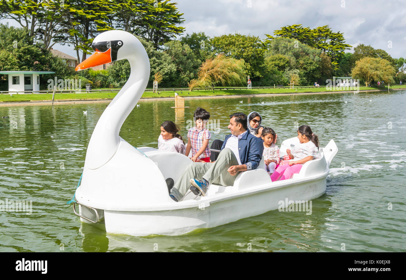 Indian family in a pedelo pedal boat on a boating lake on a cloudy Summer's day in Mewsbrook Park, Littlehampton, West Sussex, England, UK. - Stock Image