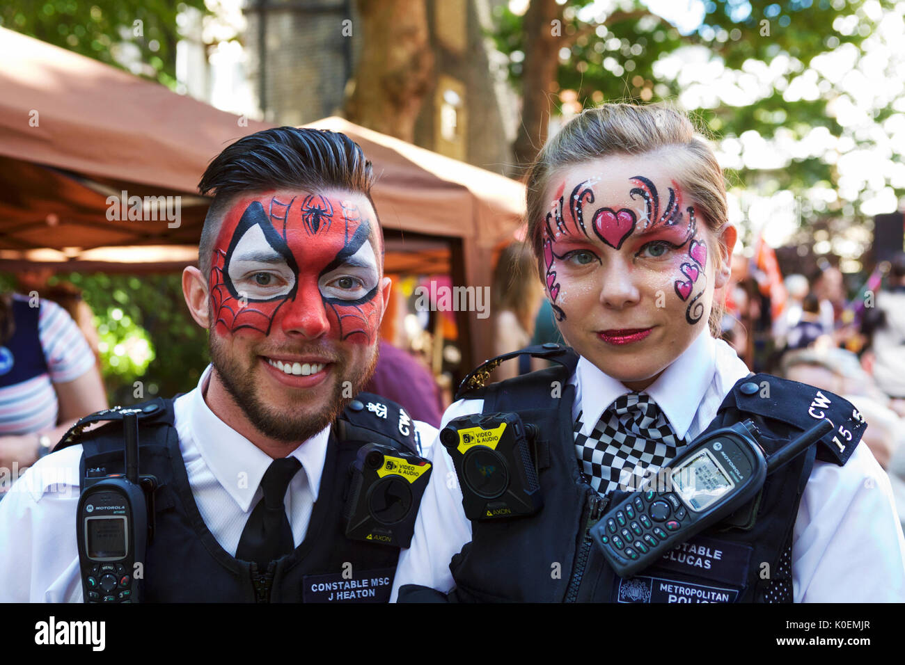 London community police officers with painted faces, at the annual Soho fete, UK. - Stock Image