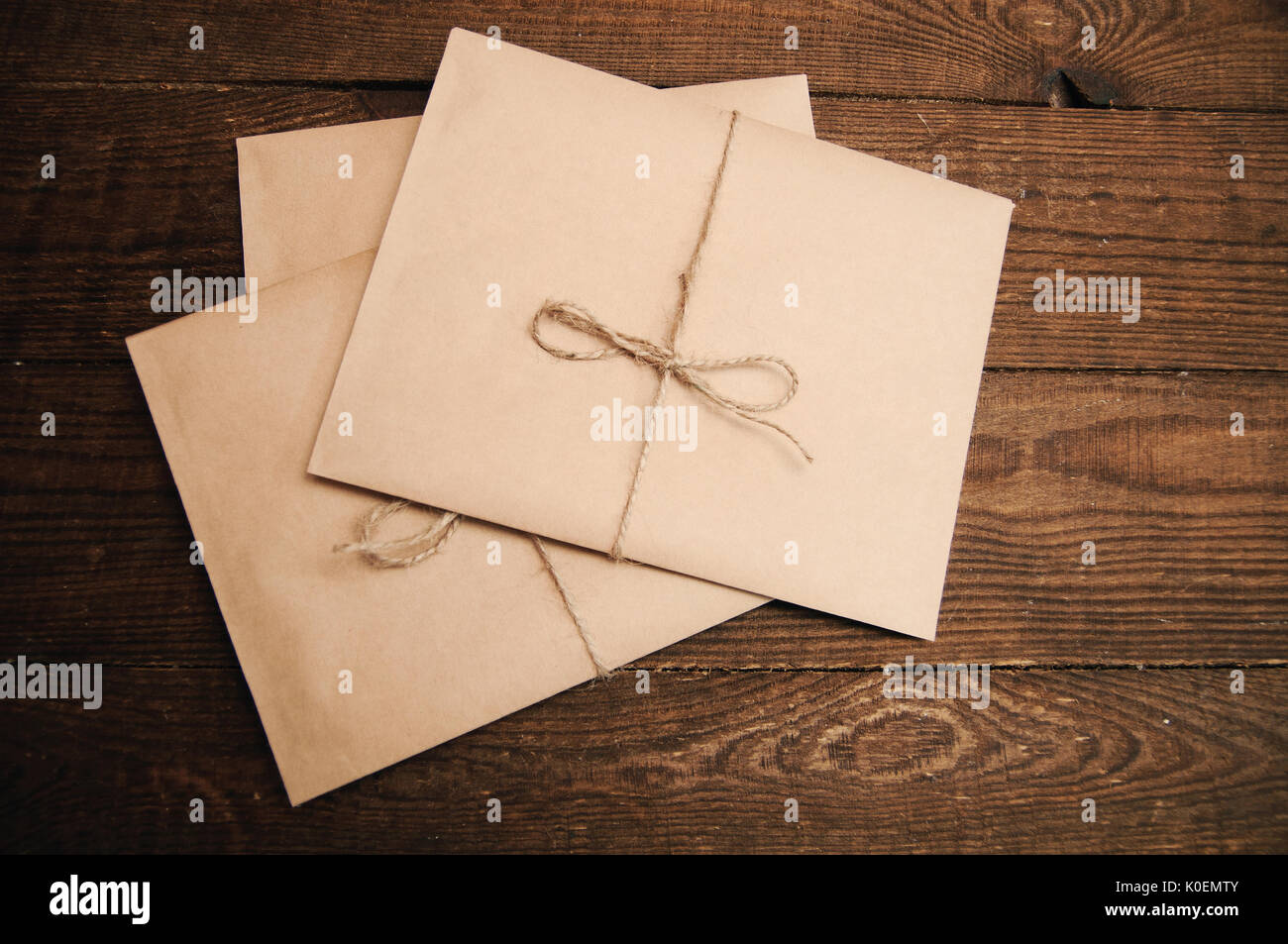 Correspondence from kraft paper on a wooden background tied with a rope - Stock Image