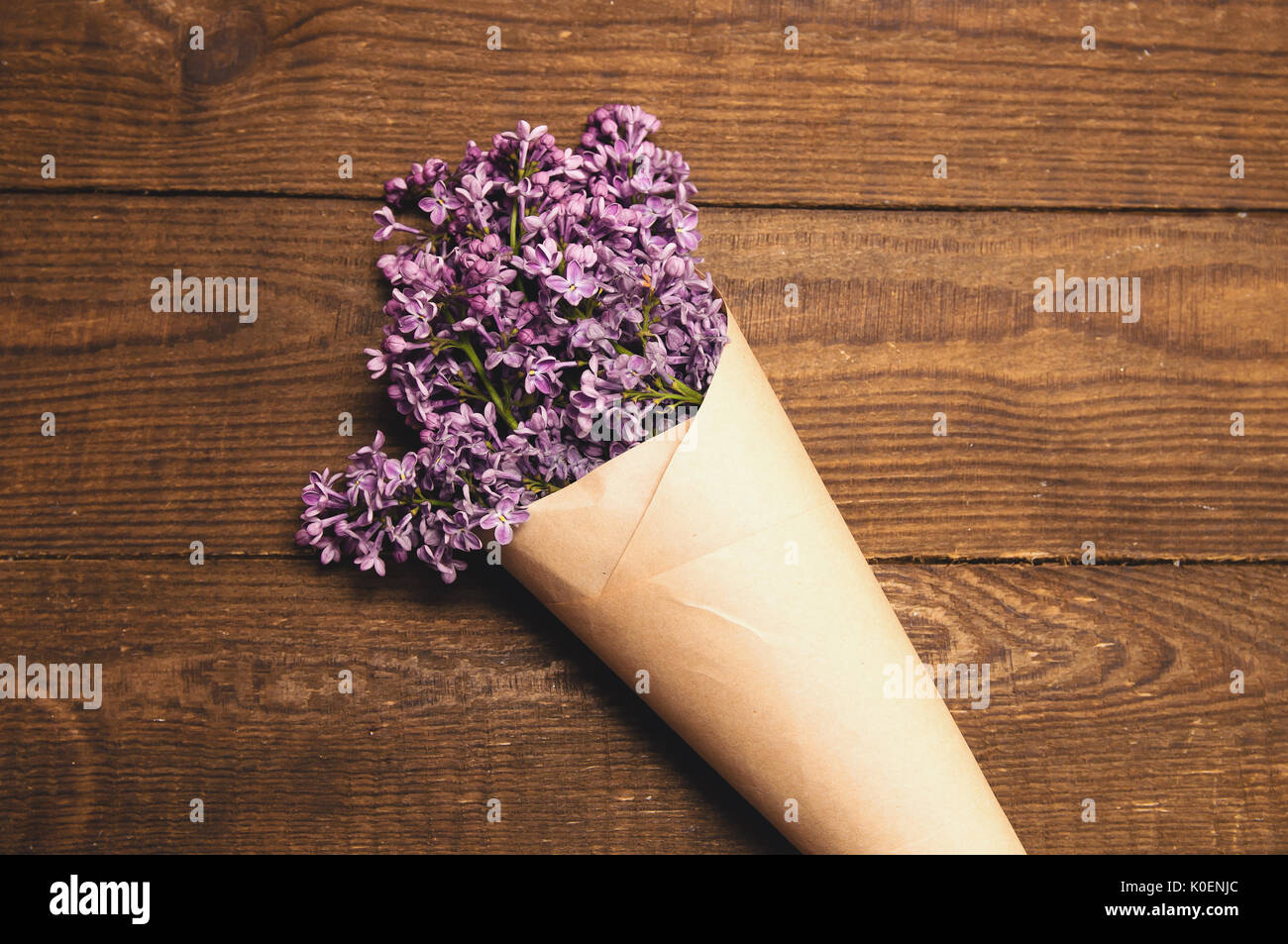 Bouquet flowers wrapped on paper stock photos bouquet flowers bouquet of lilacs on a wooden table wrapped in kraft paper stock image mightylinksfo