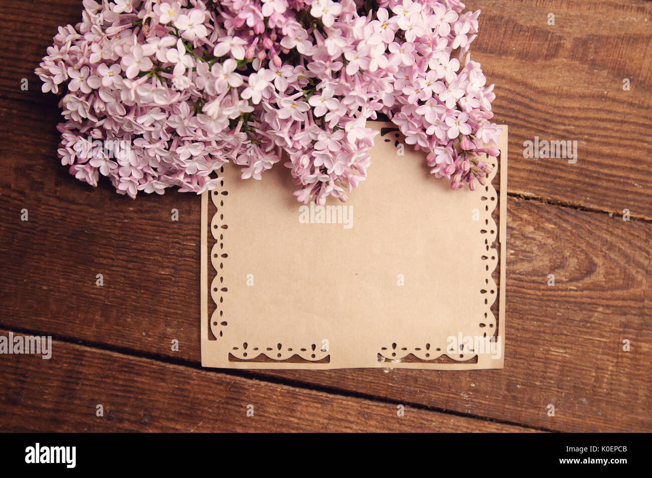 wooden table bouquet flowers of pink lilac attached greeting cards - Stock Image