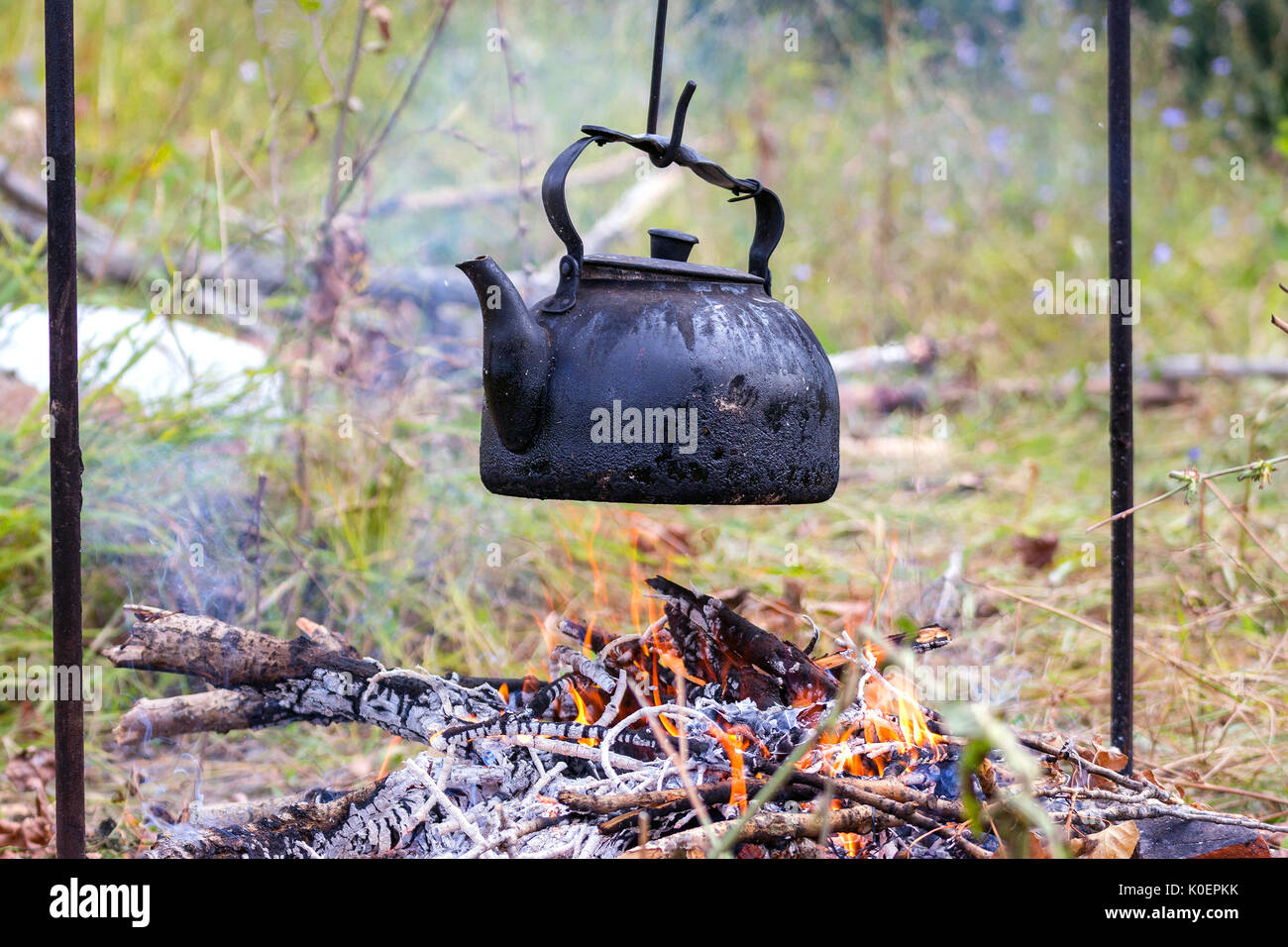 Old kettle over camp fire - Stock Image