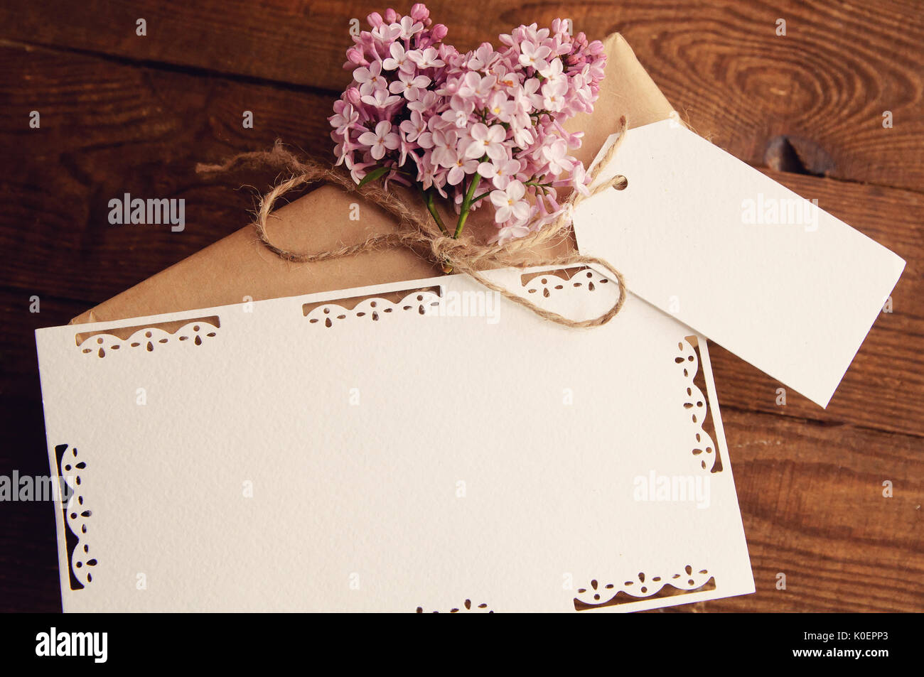 Gift wrapped with kraft paper on a wooden table, tied with a rope, with a bouquet of pink lilac, attached greeting cards - Stock Image