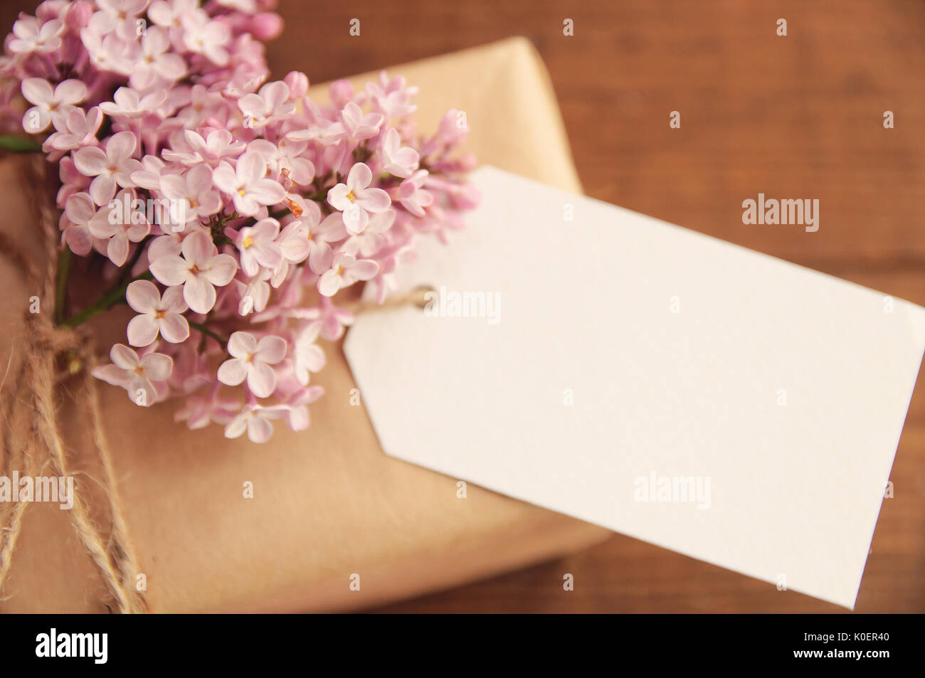 Gift wrapped with kraft paper on a wooden table, tied with a rope, with a bouquet of pink lilac, attached greeting Stock Photo