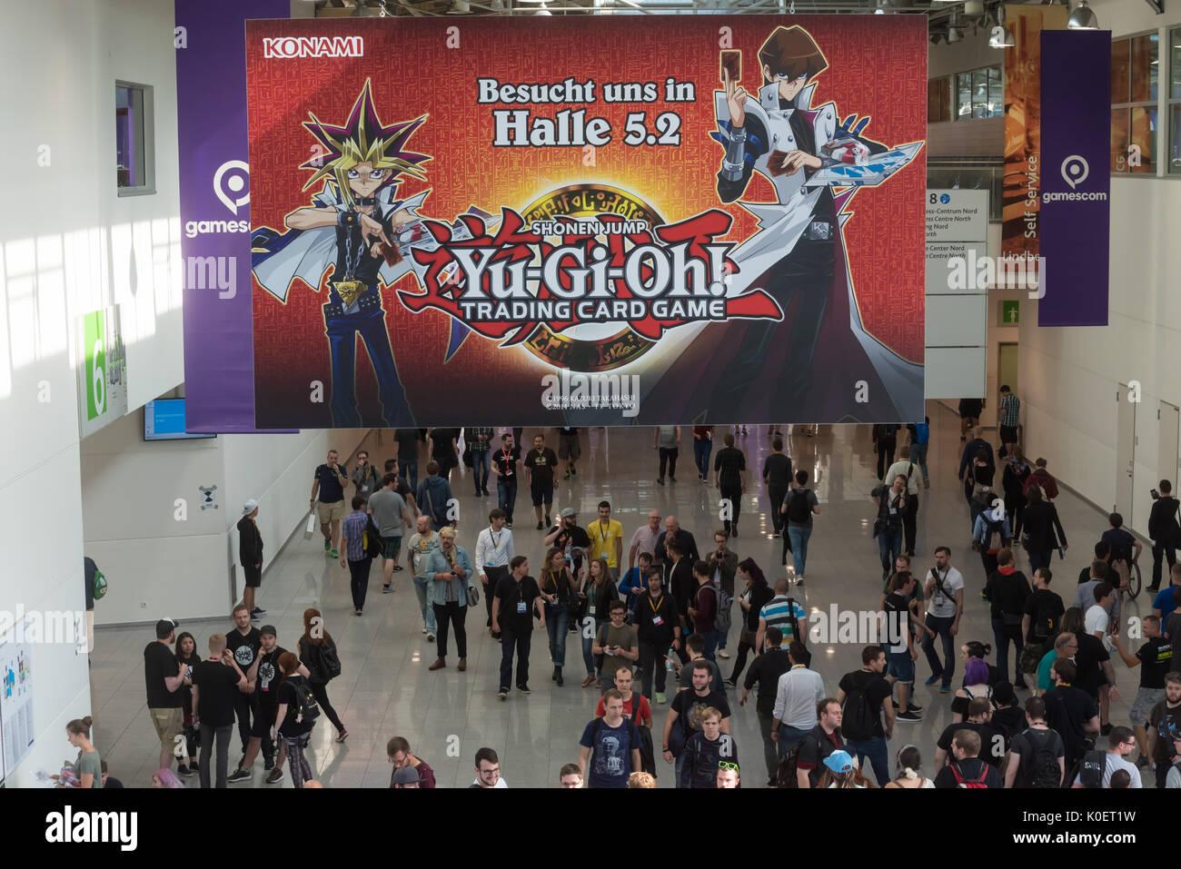 Cologne, Germany. 22nd Aug, 2017. Germany, Cologne, August 22, 2017, Gamescom: Visitors walk under Konami, yu-gi-oh, shonen jump. Credit: Juergen Schwarz/Alamy Live News - Stock Image