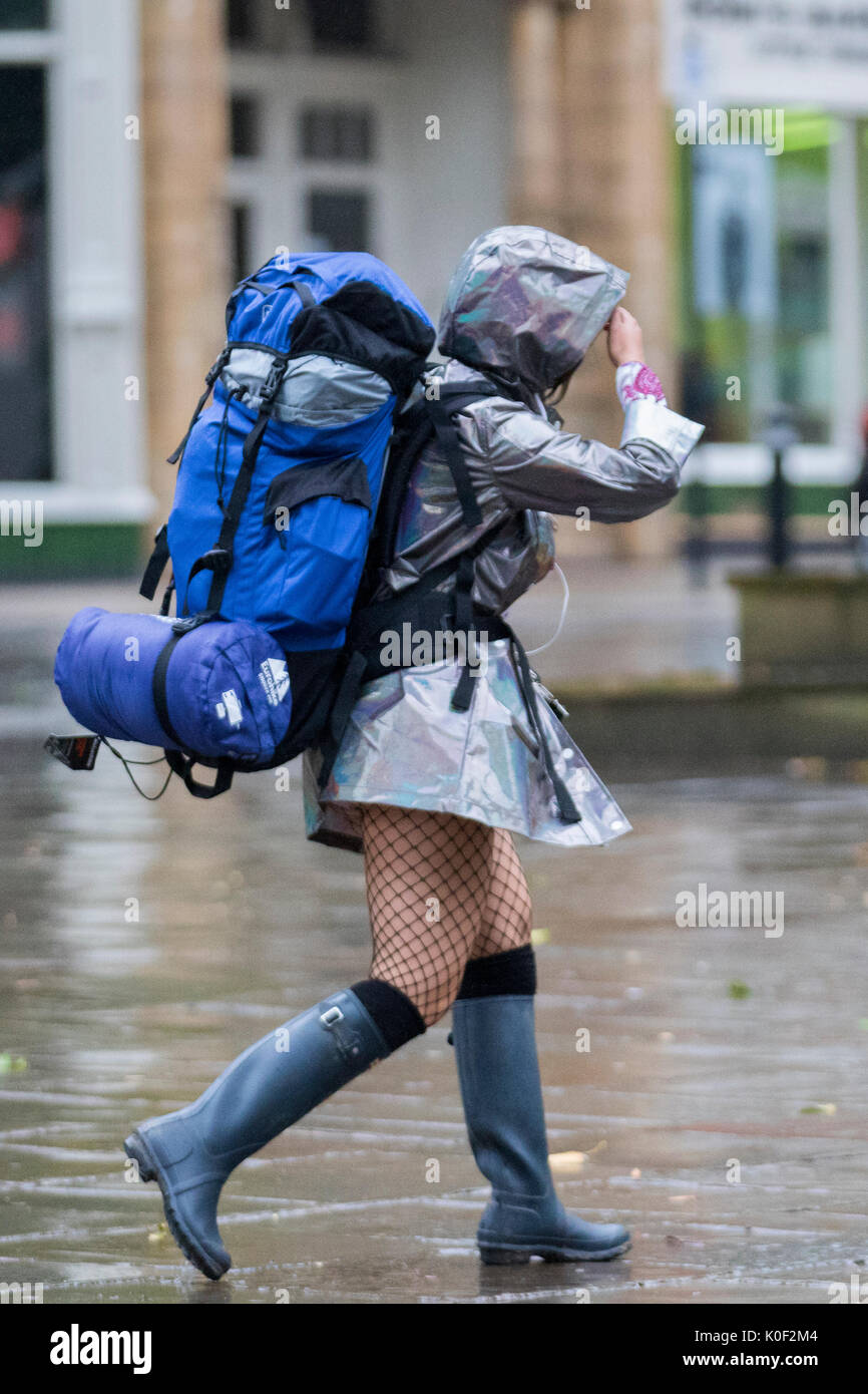 Woman with heavy haversack, wearing a short skirt and net stockings walking in the rain in Preston, Lancashire. Stock Photo