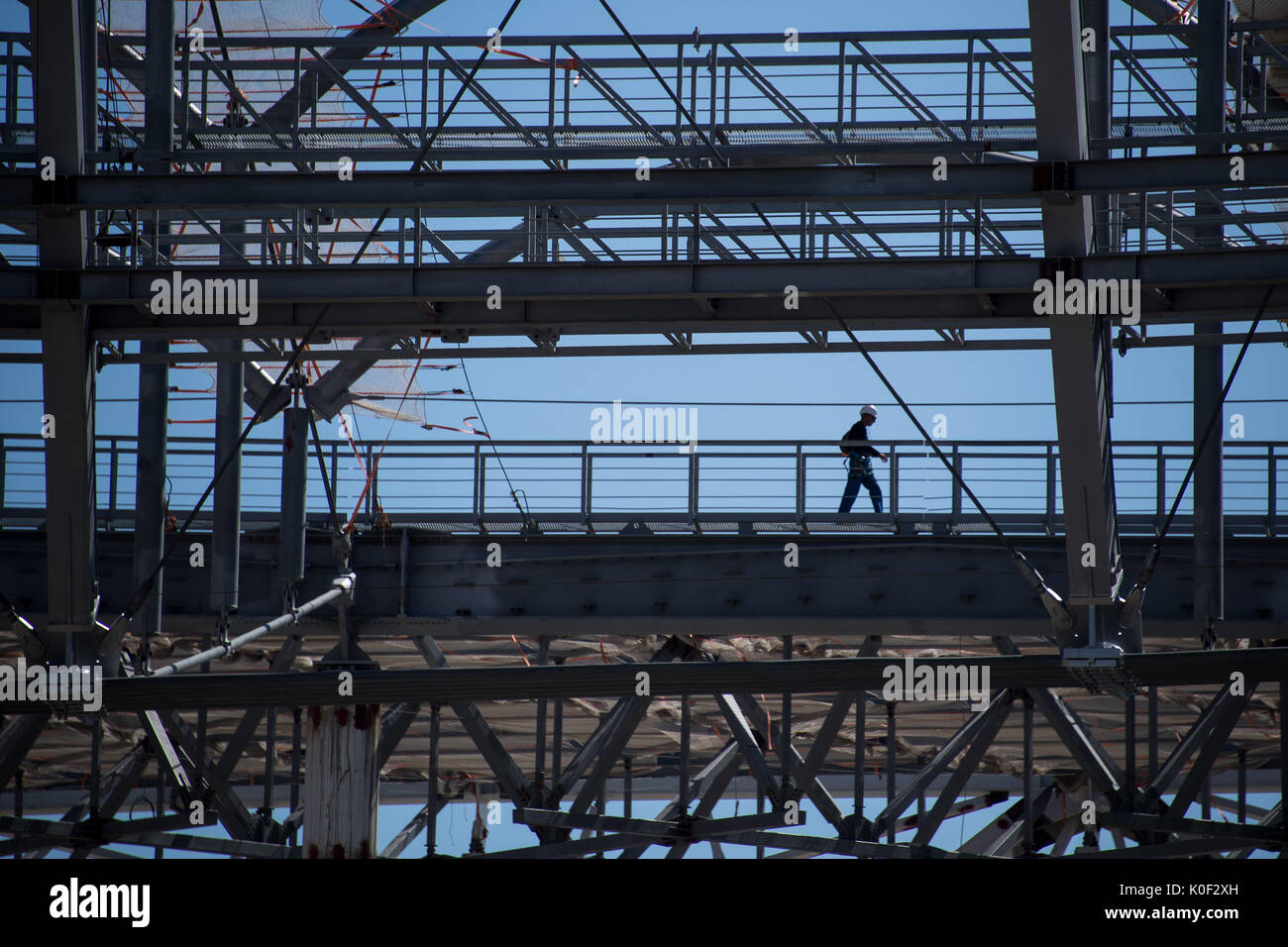 A construction worker walking through the catwalk of the