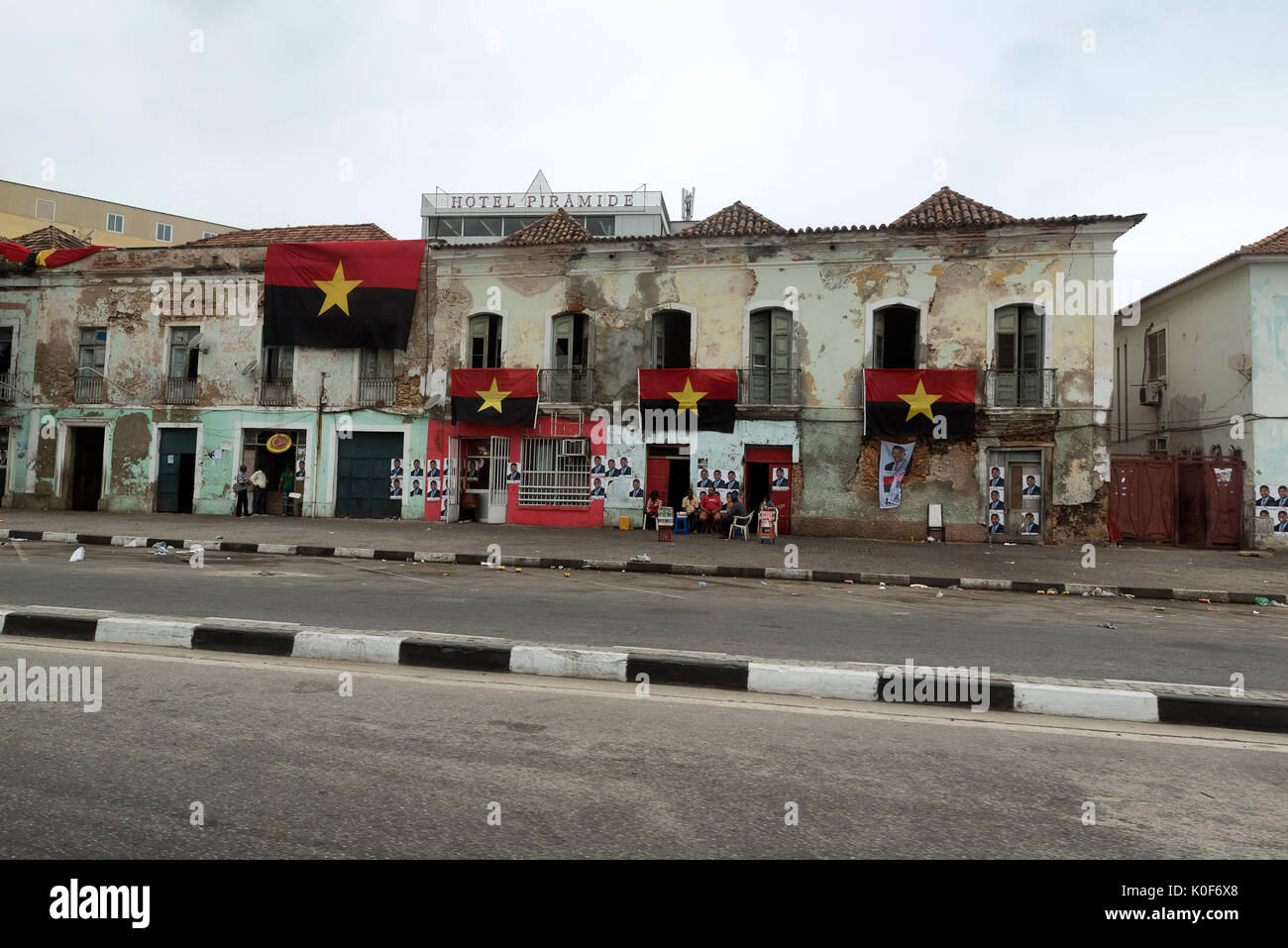 Luanda, Angola. 23rd August, 2017. Residents sit outside on election day in Angola underneath of the flags of the ruling People's Movement for the Liberation of Angola (MPLA) party and posters displaying presidential canidate Joao Lourenco. Credit: Will Reynolds Photography/Alamy Live News - Stock Image