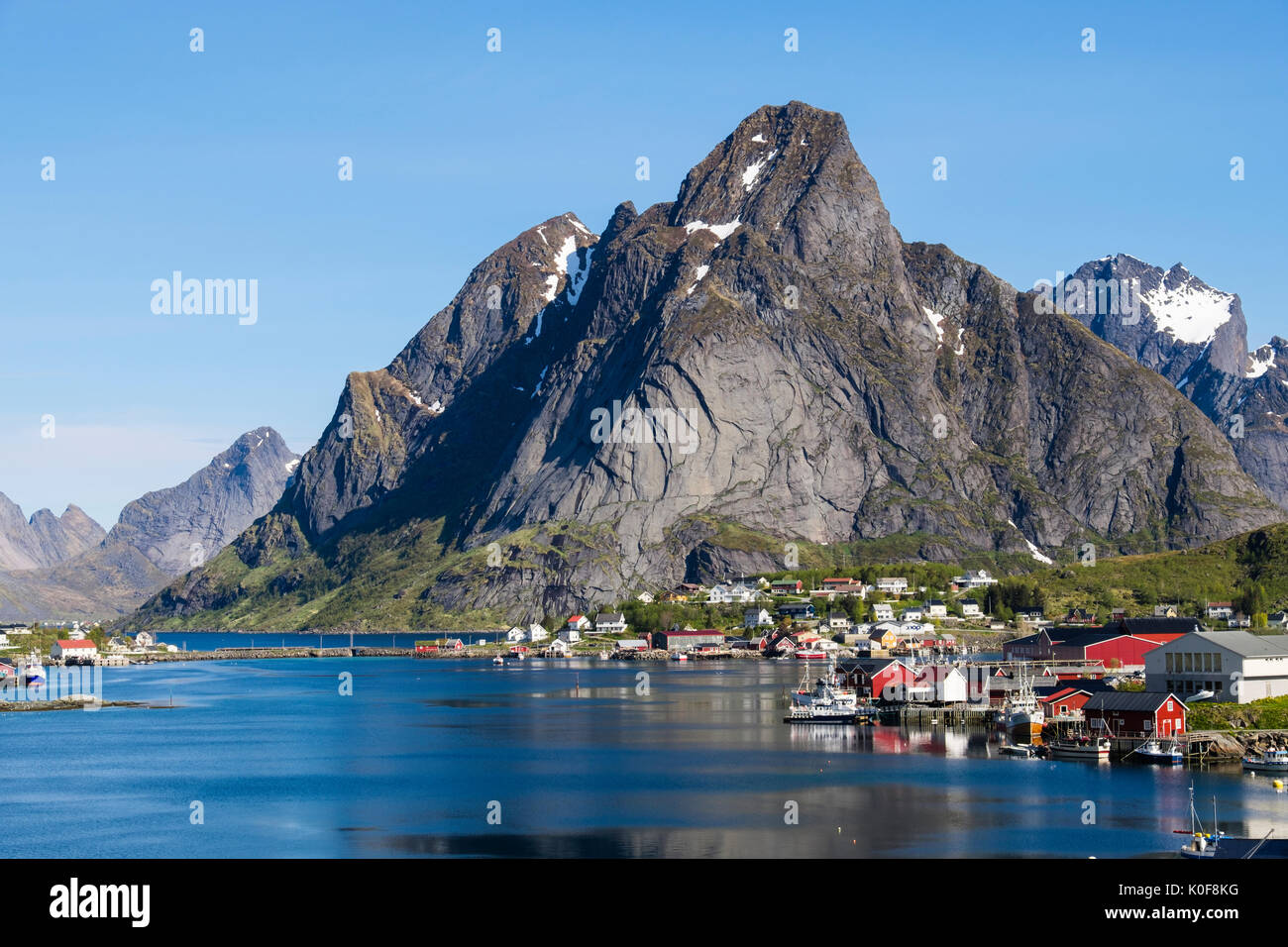 View across the natural fishing harbour to towering mountains above Reine, Moskenes, Moskenesøya Island, Lofoten Islands, Norway - Stock Image