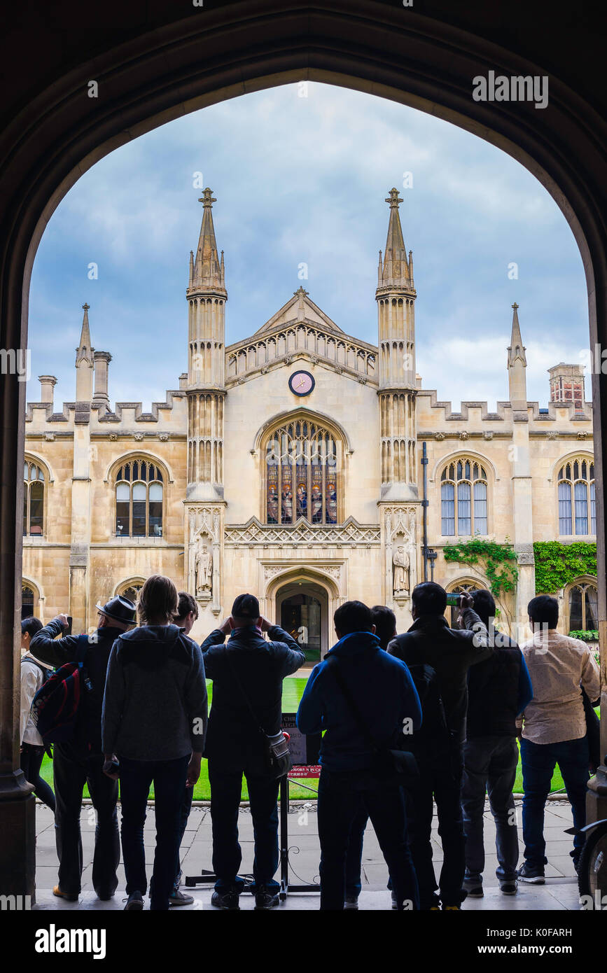 Cambridge university tourists, a group of tourists stand under the arched entrance of Corpus Christi College to look at the New Court building, UK. - Stock Image