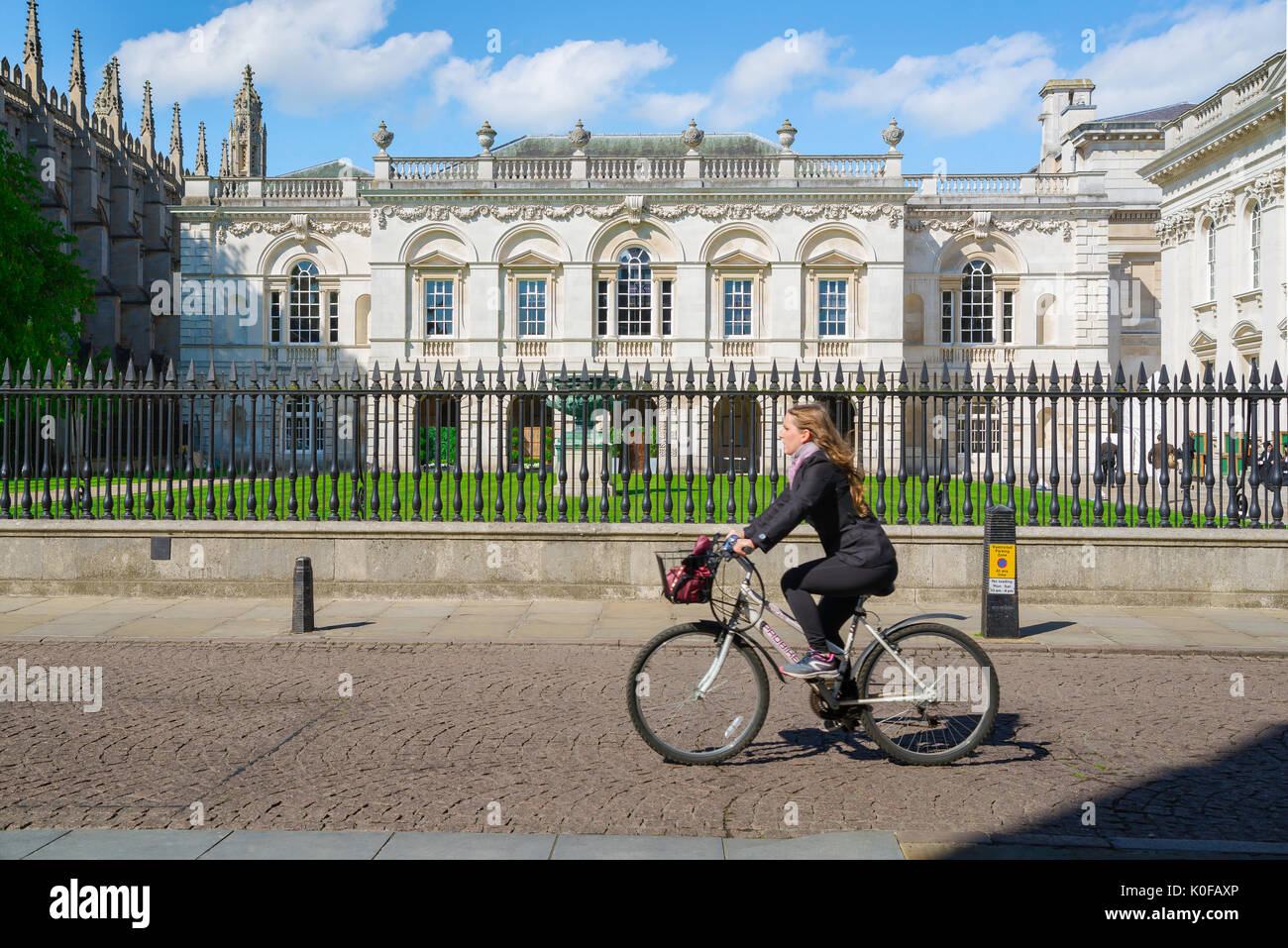 Student Cambridge University UK, a student cycles past the Old Schools Building in King's Parade in the centre of Cambridge, England. - Stock Image