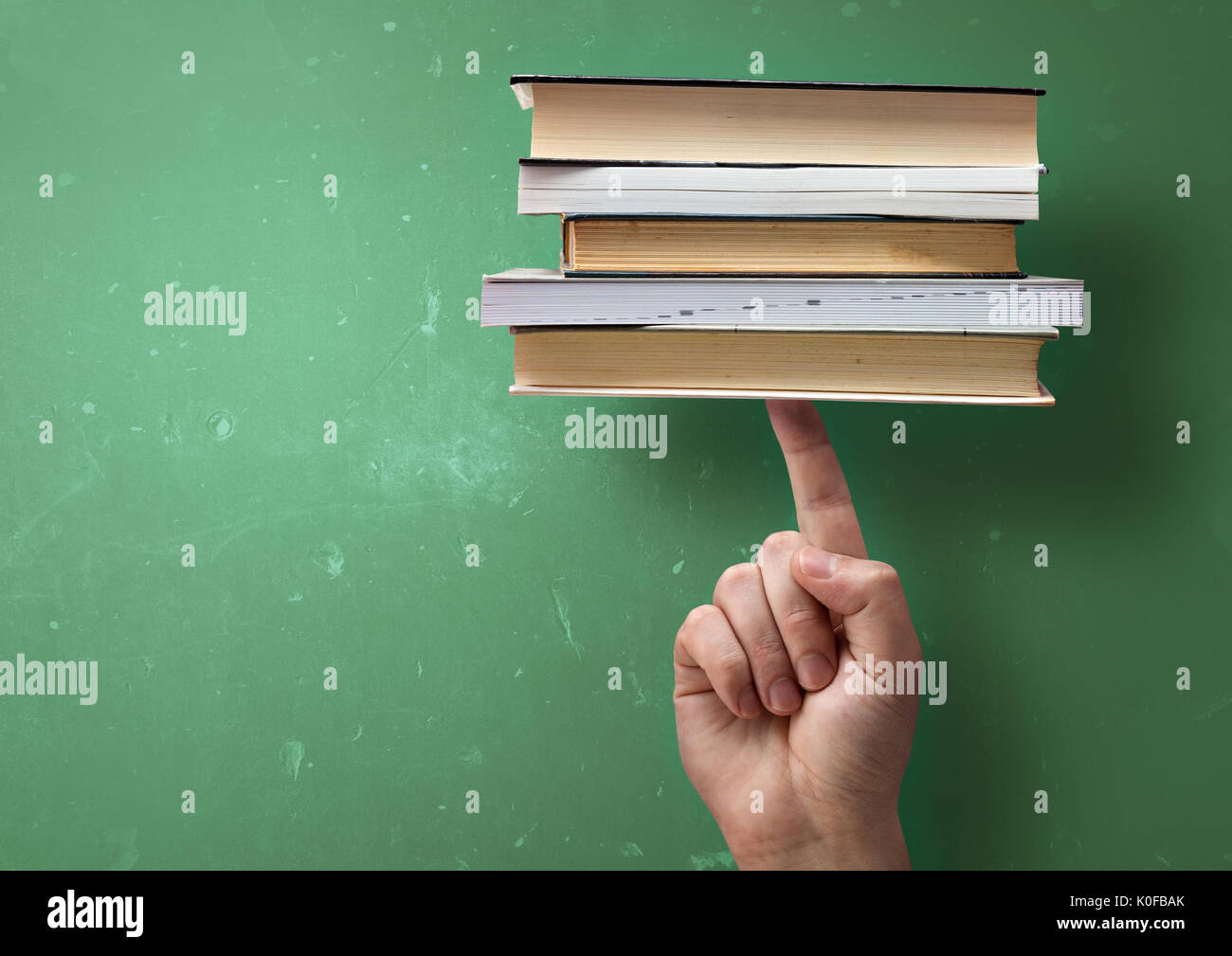 A student holding up study books with a single finger. Fast successful learning concept. - Stock Image
