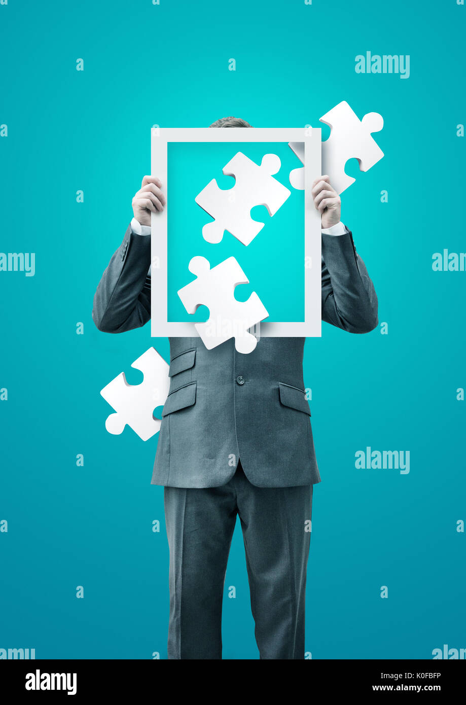 A puzzled businessman holding up a frame with puzzle pieces, business concept. - Stock Image