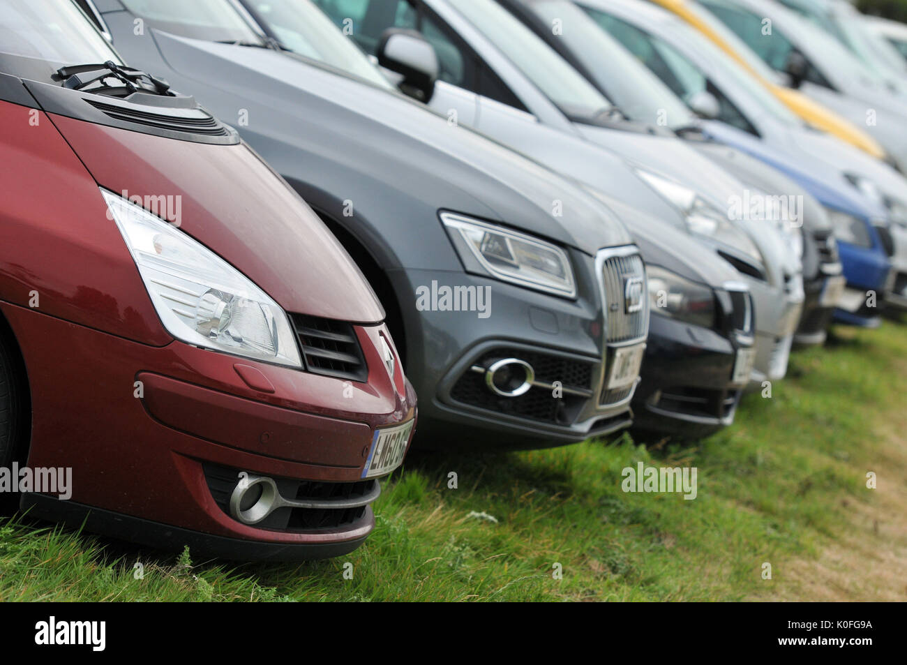 a row or line of modern cars parked in a row in a field or carpark different colours headlights and bumpers on the - Stock Photo