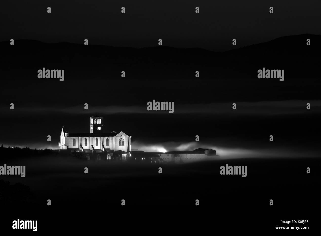 Beautiful night view of St. Francis church (Assisi, Umbria) over a sea of fog - Stock Image