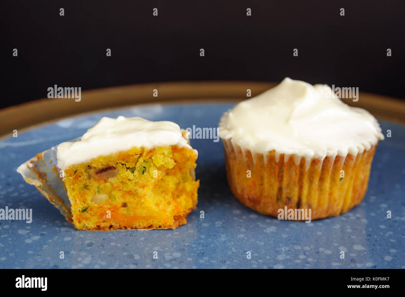 Zucchini and carrot cupcakes with Philadelphia cheese cream on blue plate on black surface - Stock Image