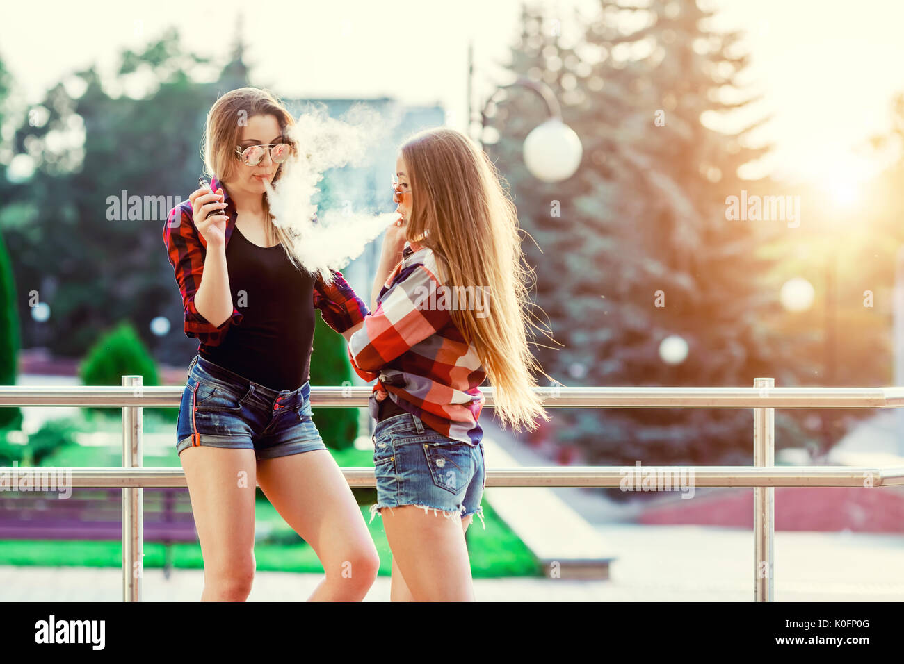 Two women vaping outdoor. The evening sunset over the city. Toned image. - Stock Image