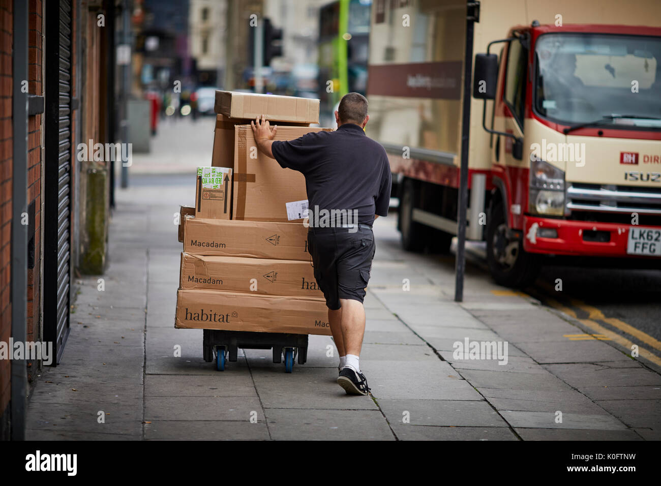 A delivery van parks no the pavement and double yellow line as a courier delivers large boxes by hand trolly - Stock Image