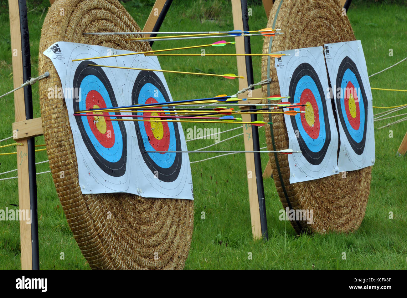 traditional archery targets for bow and arrow shooting competitions with arrows sticking into the bulls eye and inner and outer rings of the targets - Stock Image