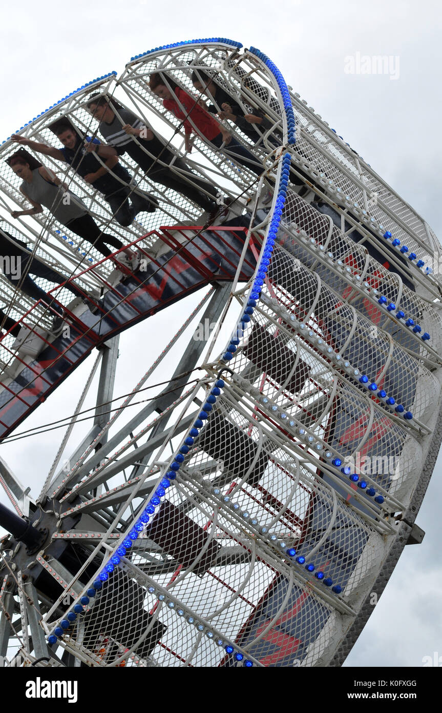 a fairground ride using centrifugal force to pin the riders to the sides of a giant wheel at an angle spinning in the air and frightening the riders. - Stock Image