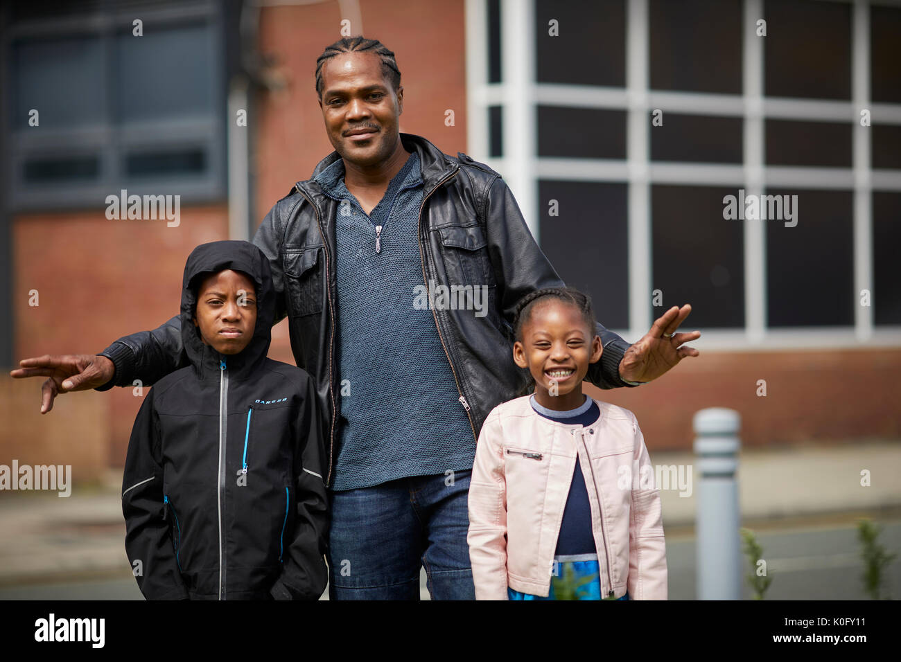 Local black man possesses with his children in Moss Side South Manchester suburb - Stock Image