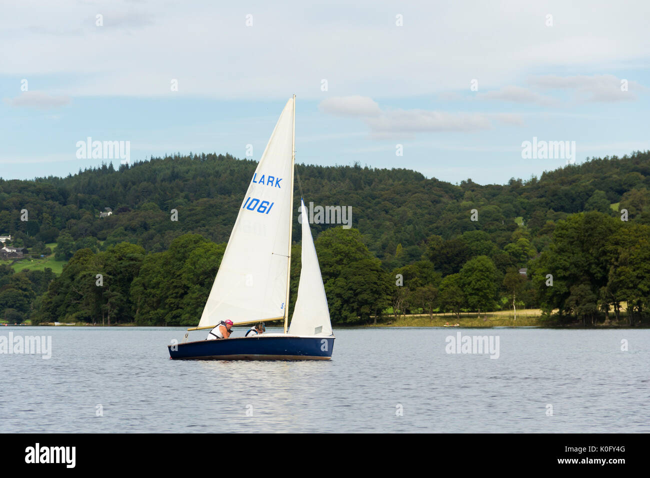 Lark class sailing dinghy in full sail on the water at the north end of Coniston Water. - Stock Image