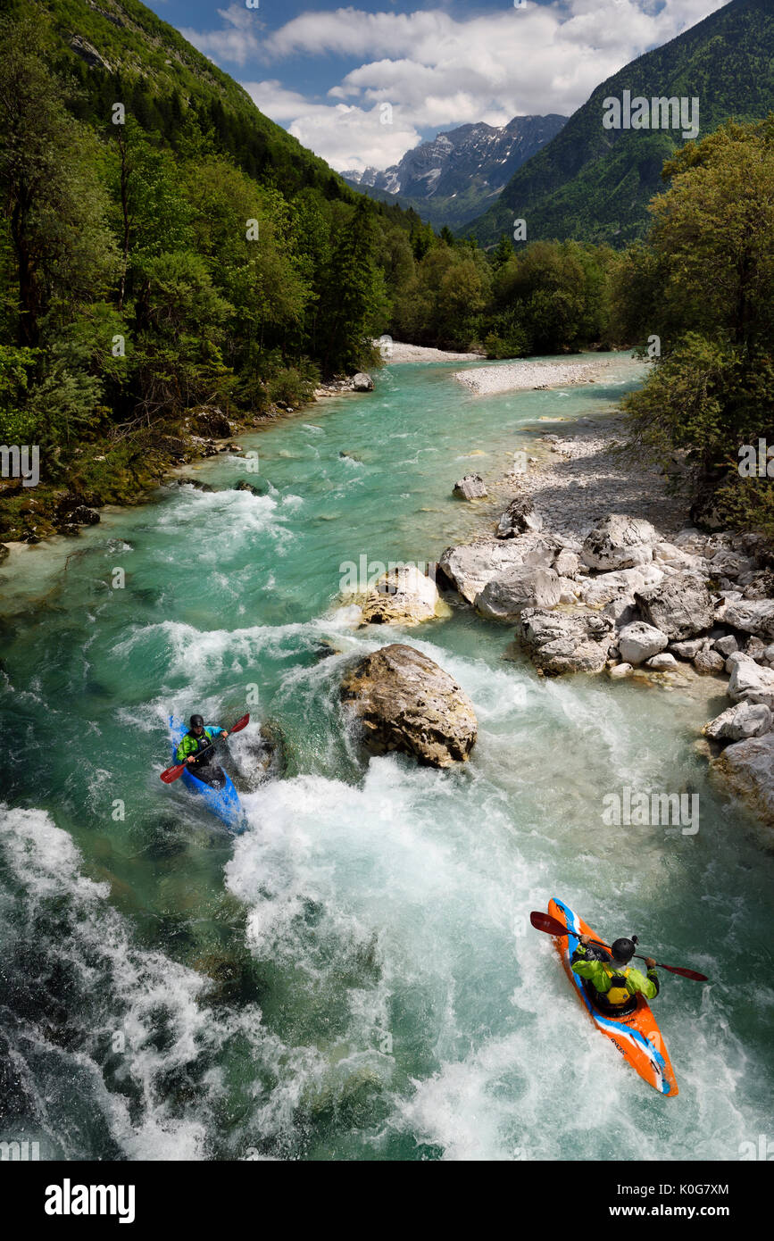 Kayakers shooting the cold emerald green alpine water of the Upper Soca River near Bovec Slovenia with Veliko Spicje Stock Photo