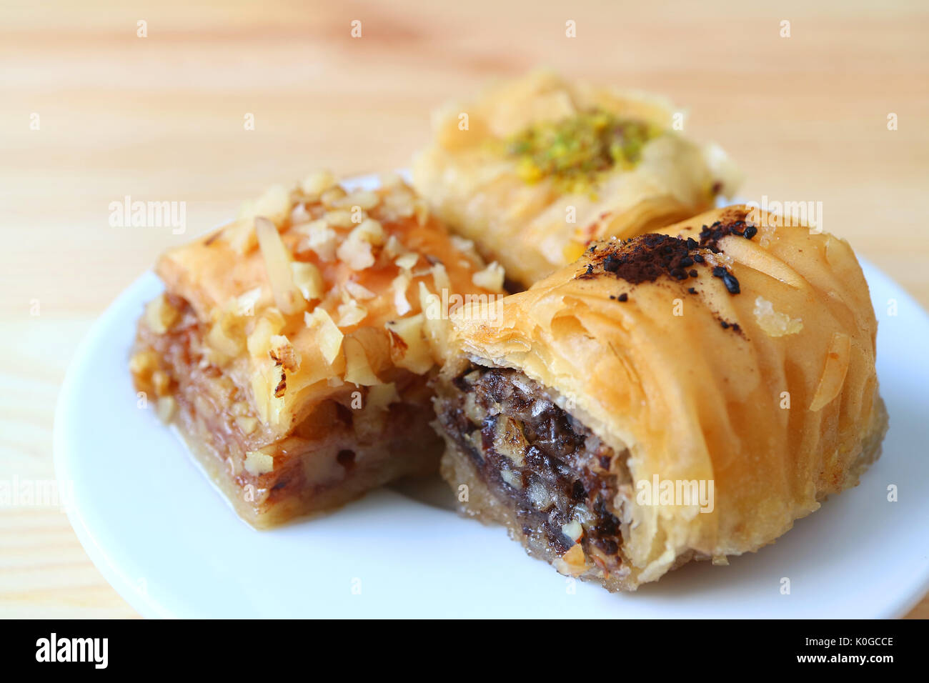 Closed up Three Types of Baklava Sweets on White Plate Served on Wooden Table, Blurred Background Stock Photo