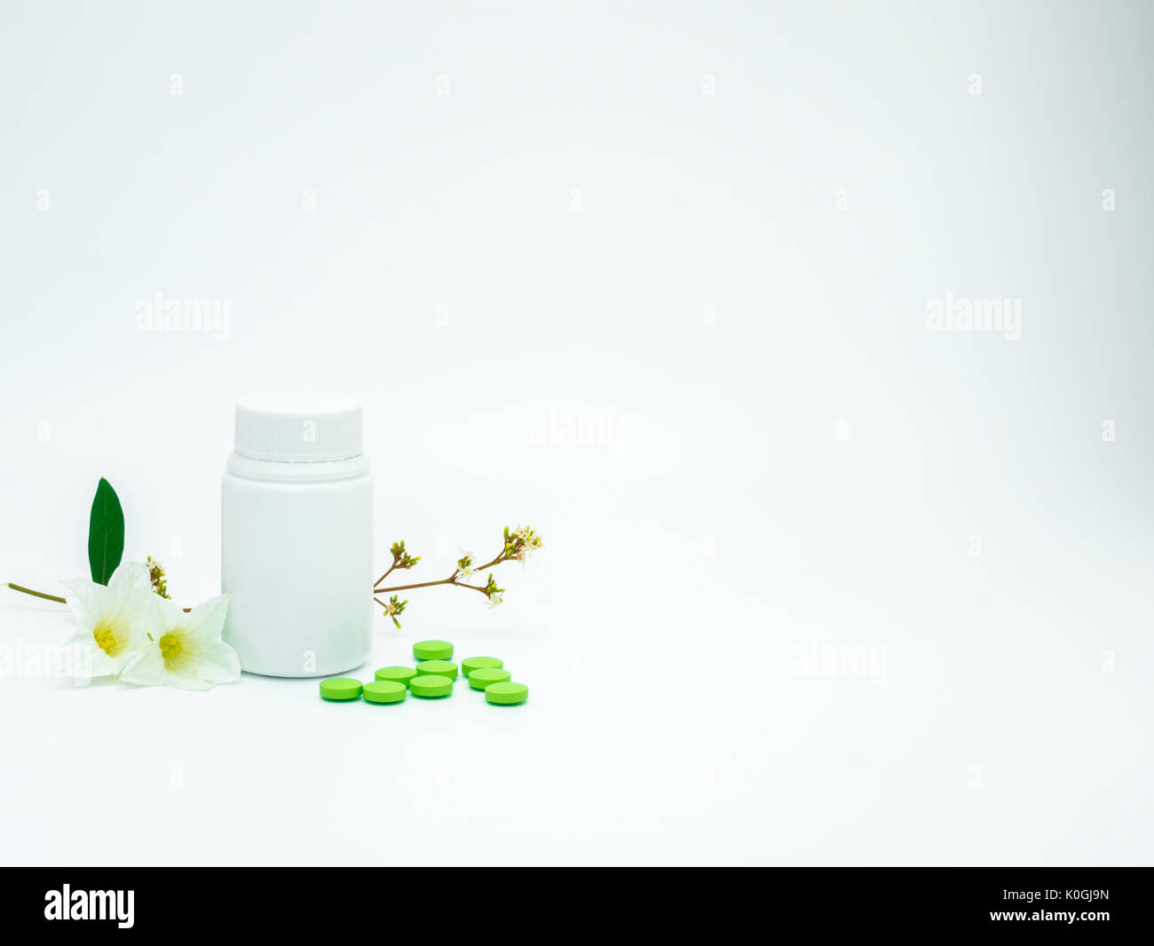 Green vitamin and supplement tablet pills with flower and branch and blank label plastic bottle on white background with copy space, just add your own - Stock Image