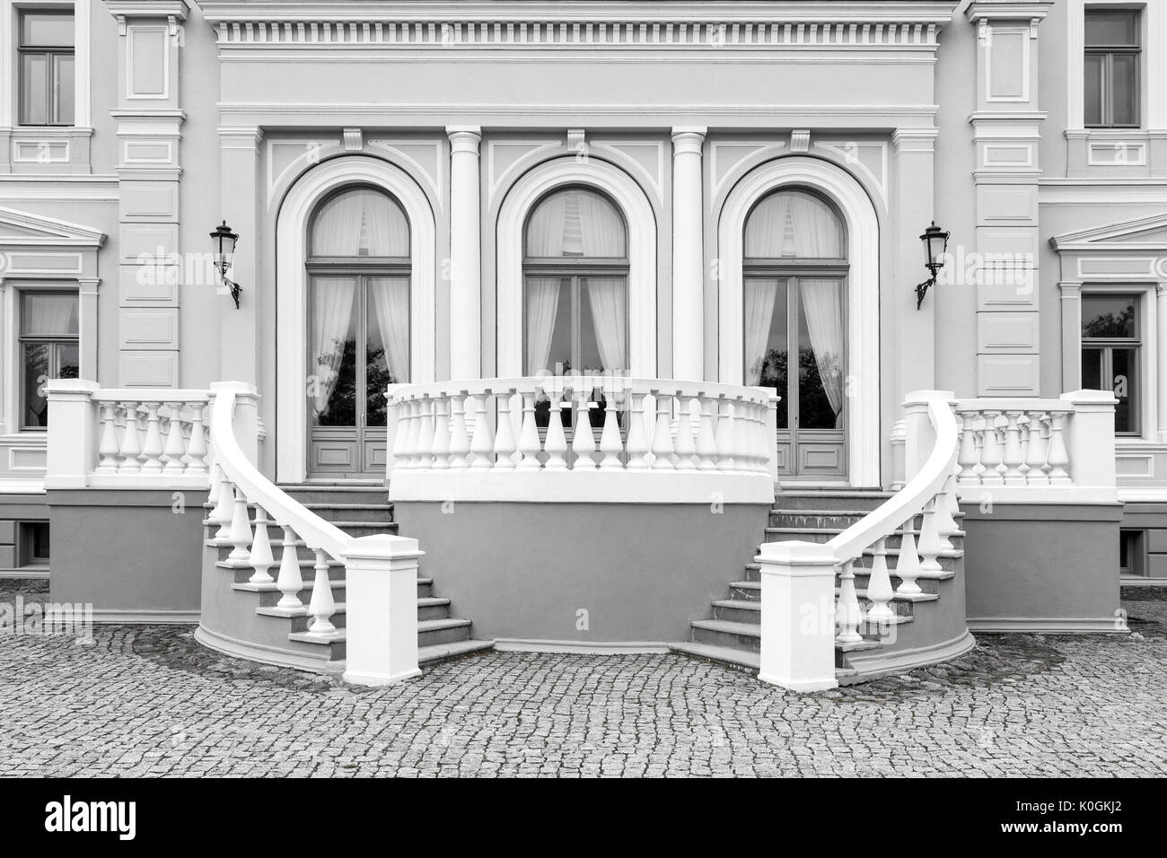 Exterior detail of an old neo renaissance building with stairs and windows, black and white picture - Stock Image