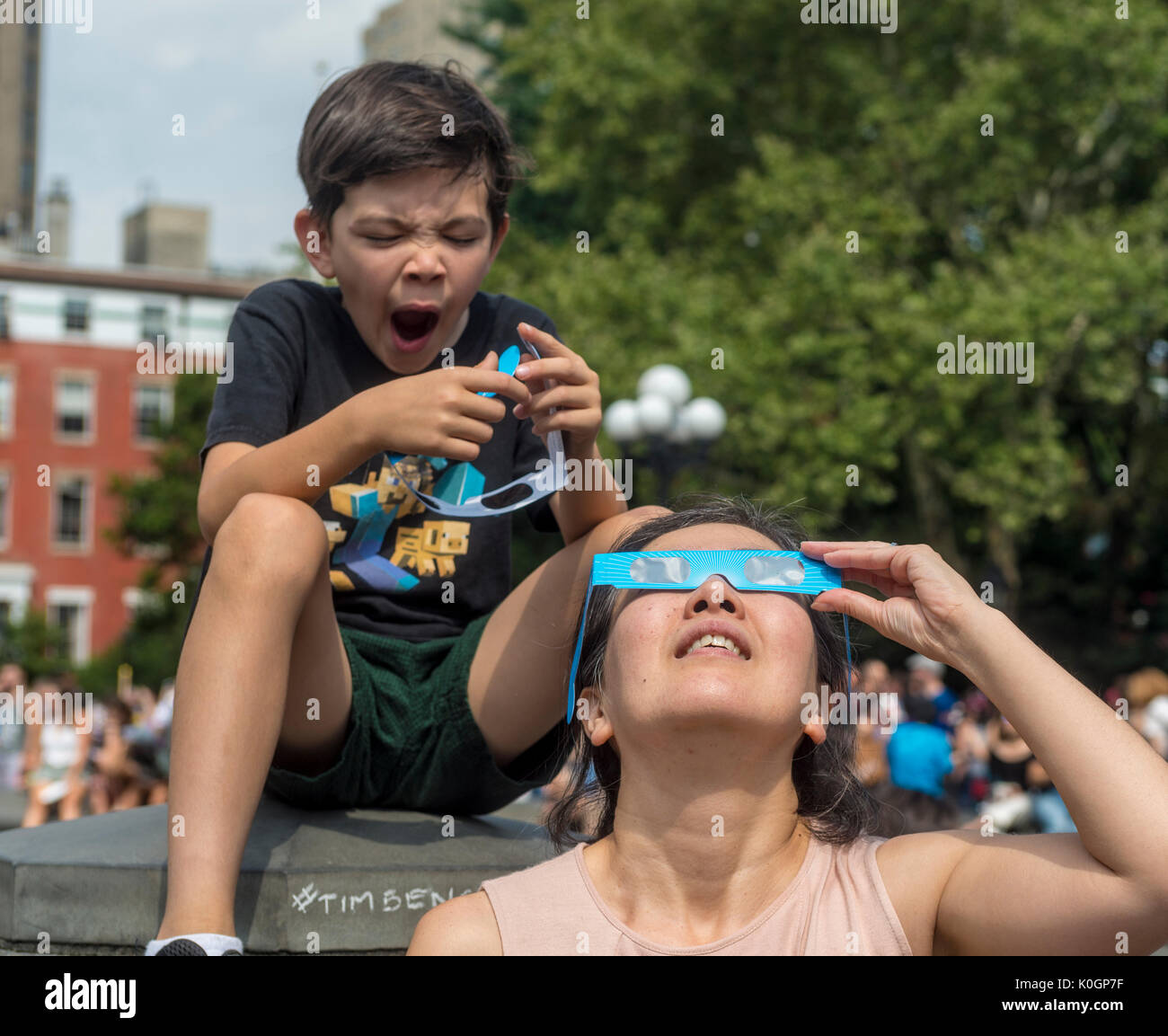 New York, NY 21 August 2017 - As mom watches the eclipse a young boys grows impatient. New Yorkers gathered in Washington Stock Photo
