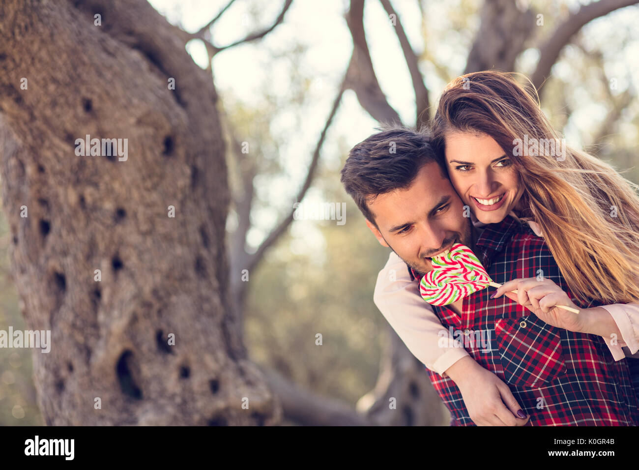 Portrait of smiling handsome man giving piggy back to his girlfriend in the nature - Stock Image