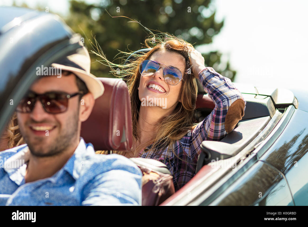 Group of cheerful young friends driving car and smiling in summer - Stock Image