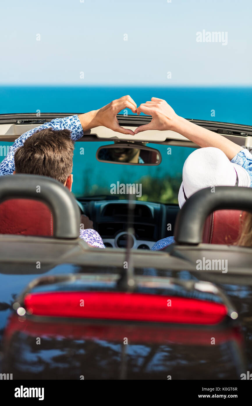 Happy young lover couple make heart shape on road trip in convertible car. - Stock Image