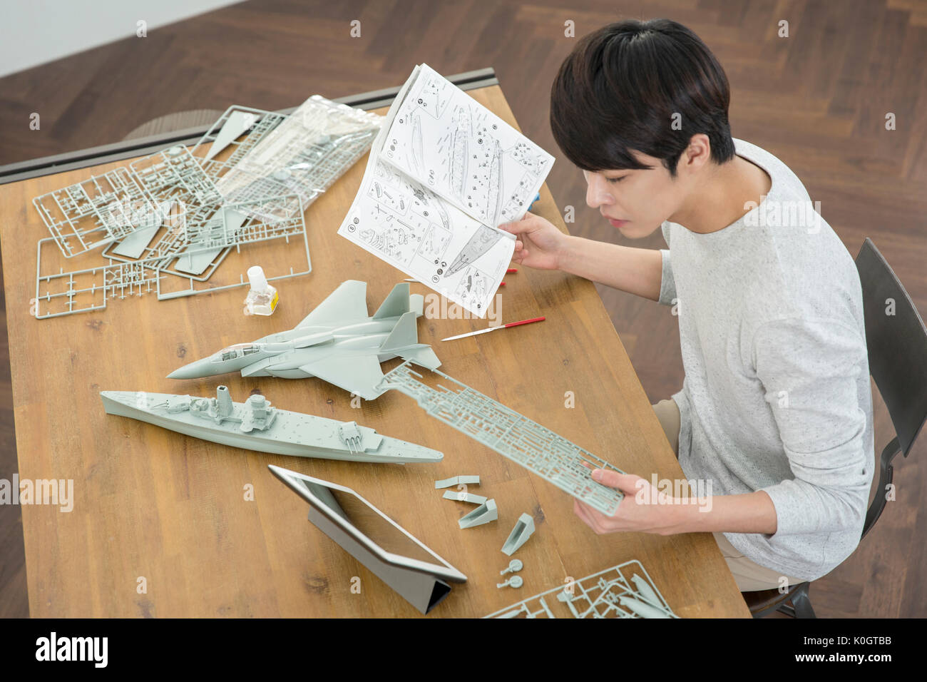 Portrait of male kidult making a model airplane Stock Photo