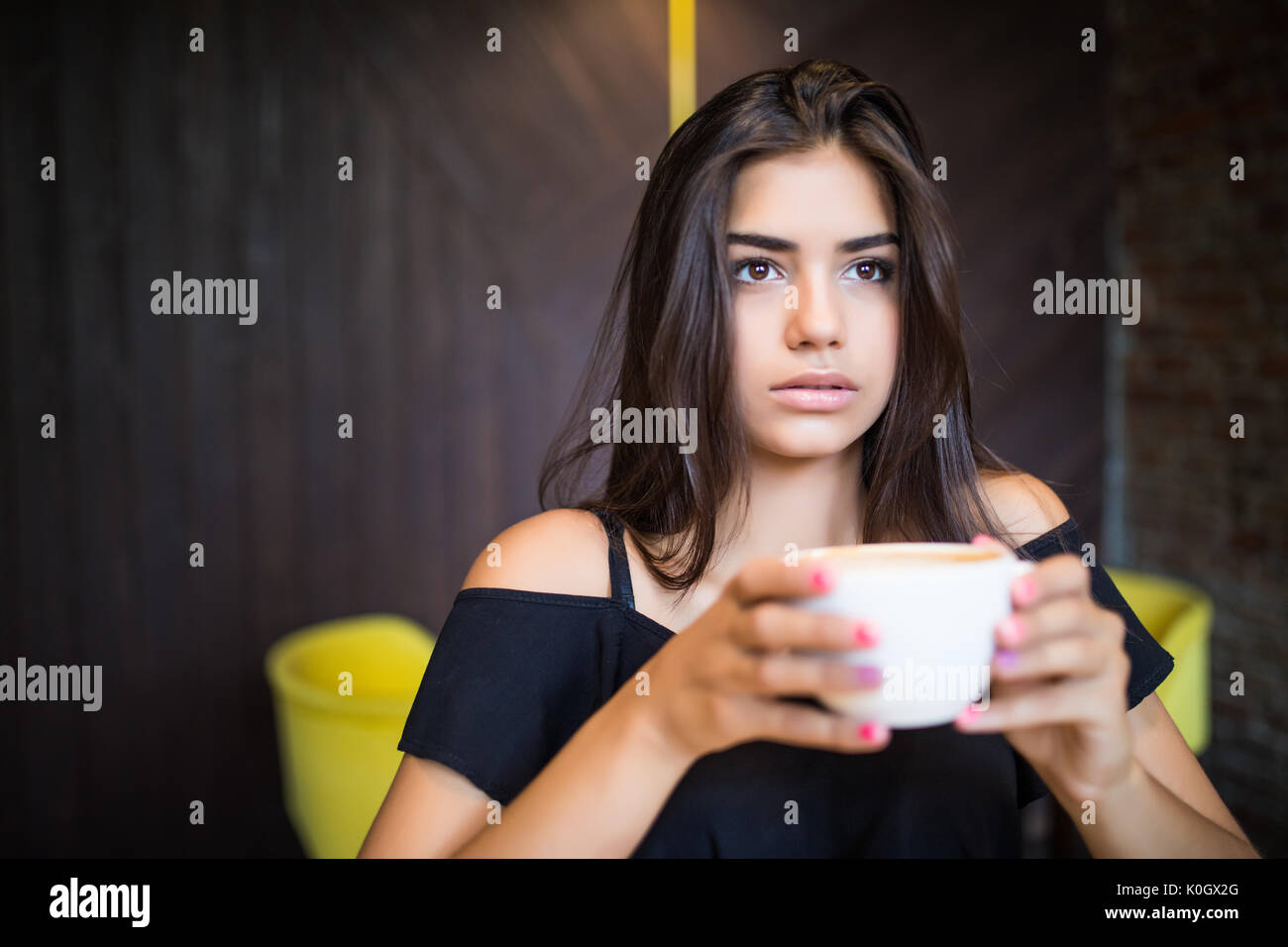 Woman with cup of tea has a rest at the coffee bar - Stock Image
